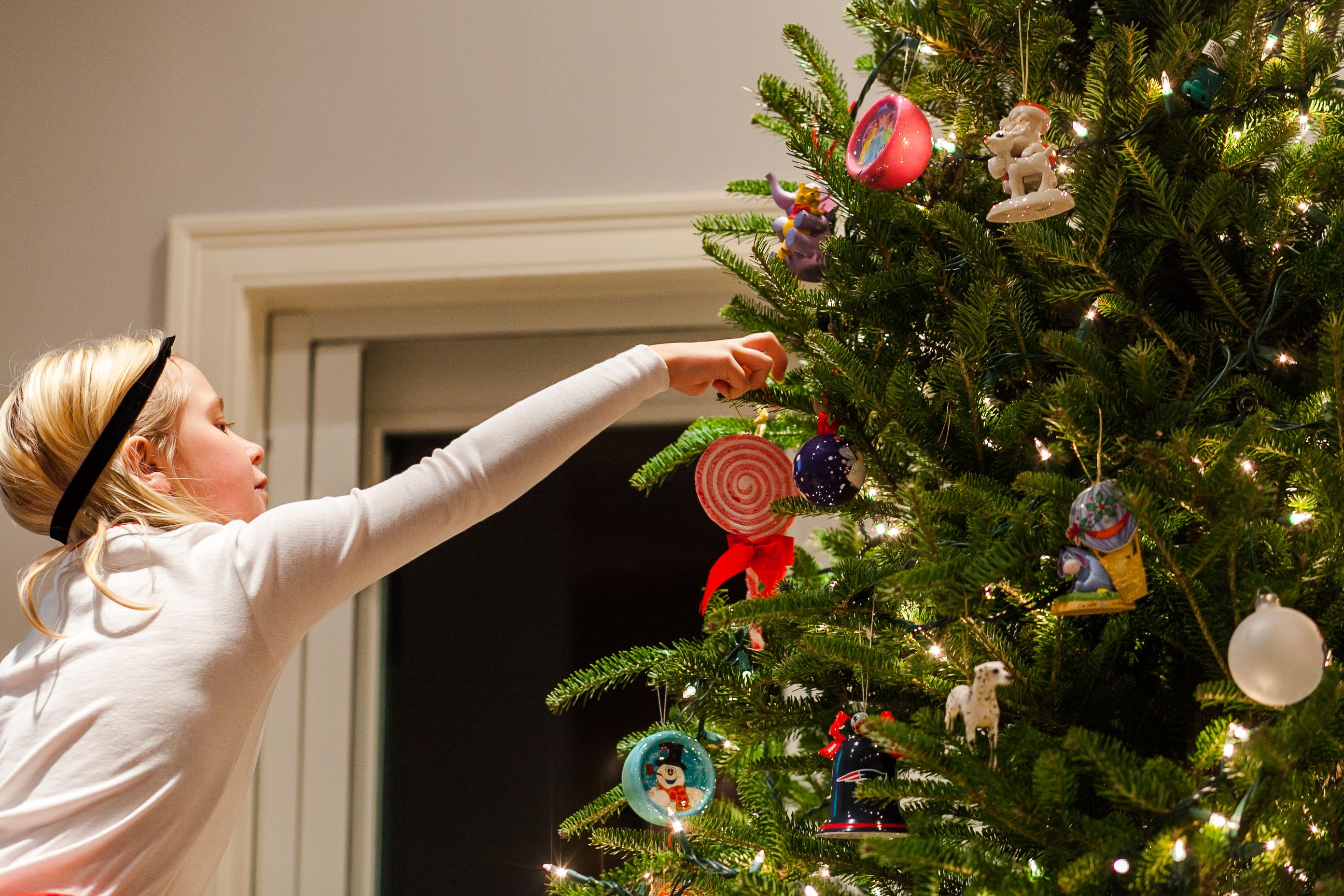 girl hanging red and white ornament on Christmas tree