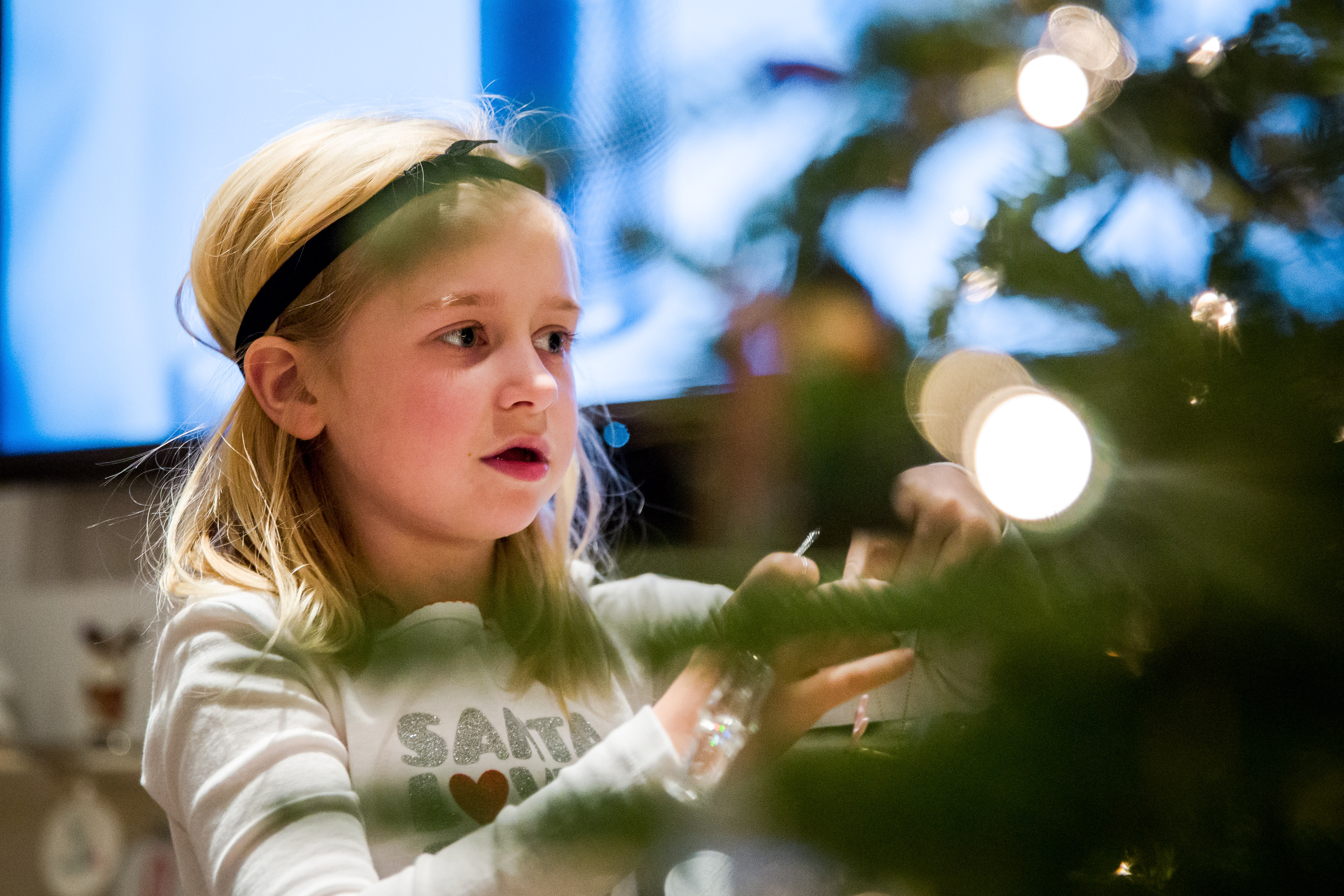 Looking through tree at little girl and lights
