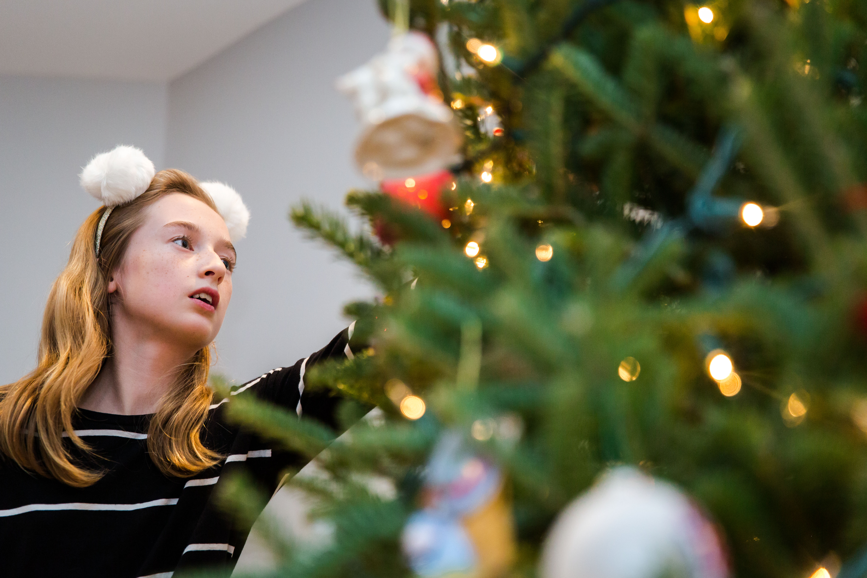 girl wearing white pom pom headband looking at Christmas tree