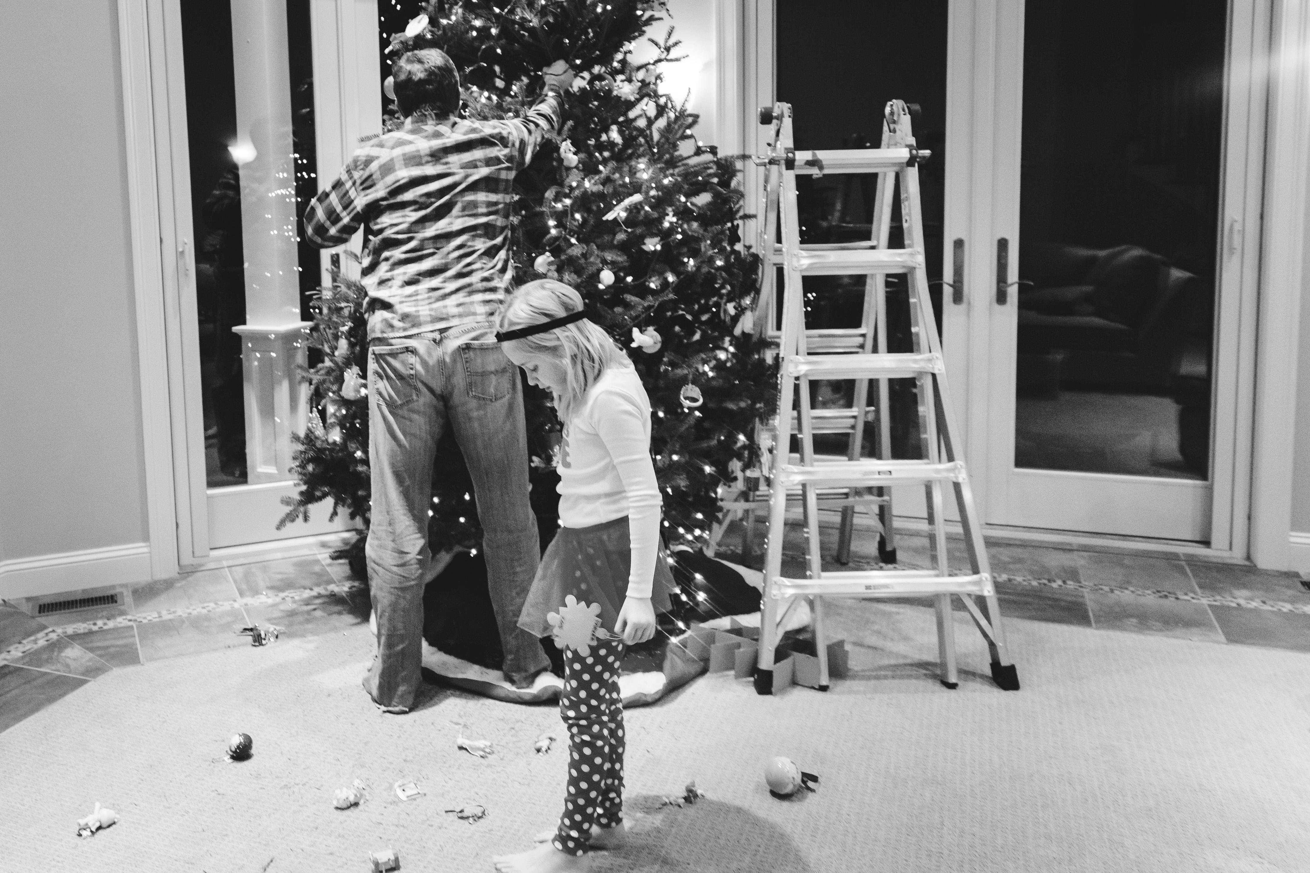 little girl looking at broken ornaments on floor
