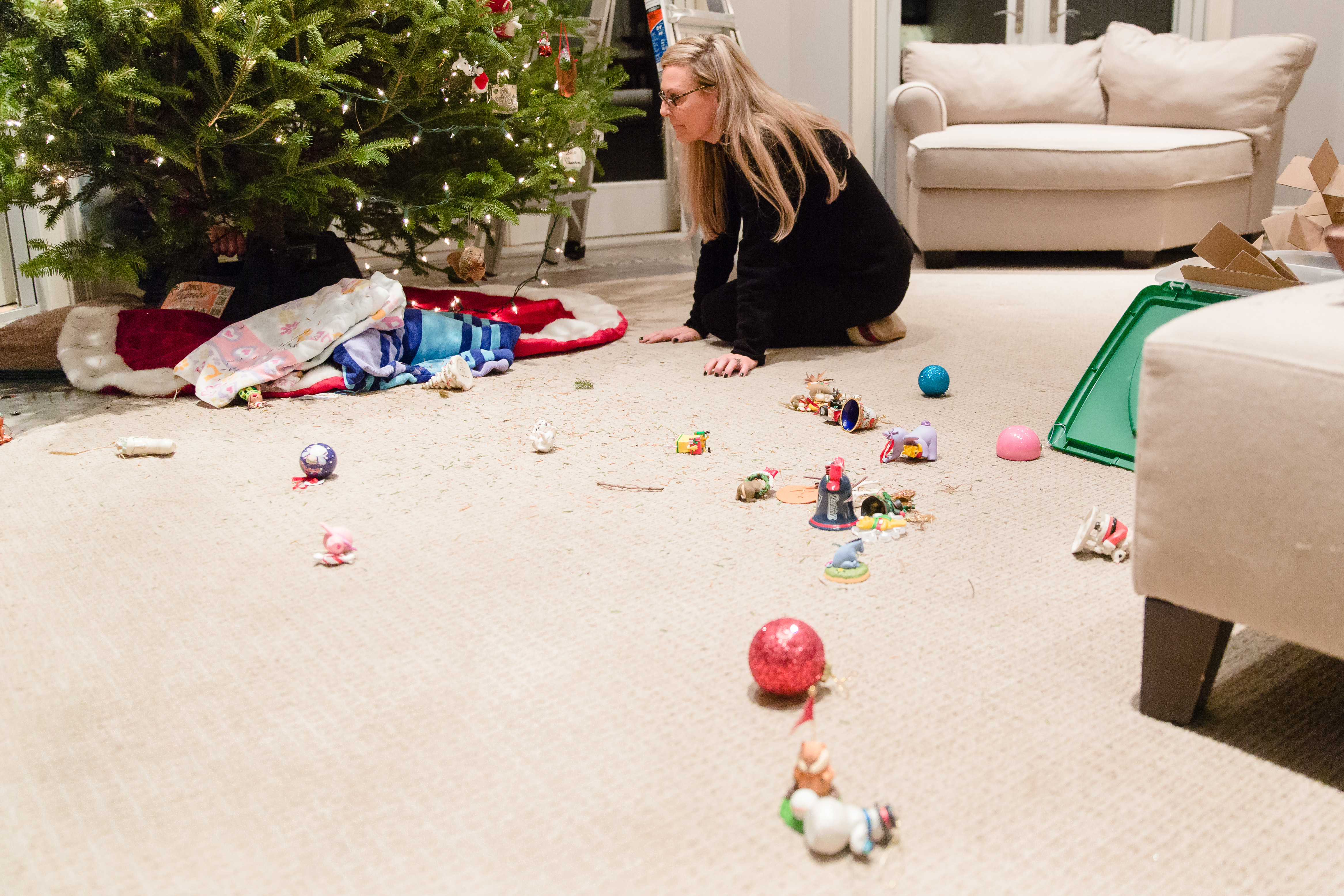mom on floor cleaning up broken ornaments