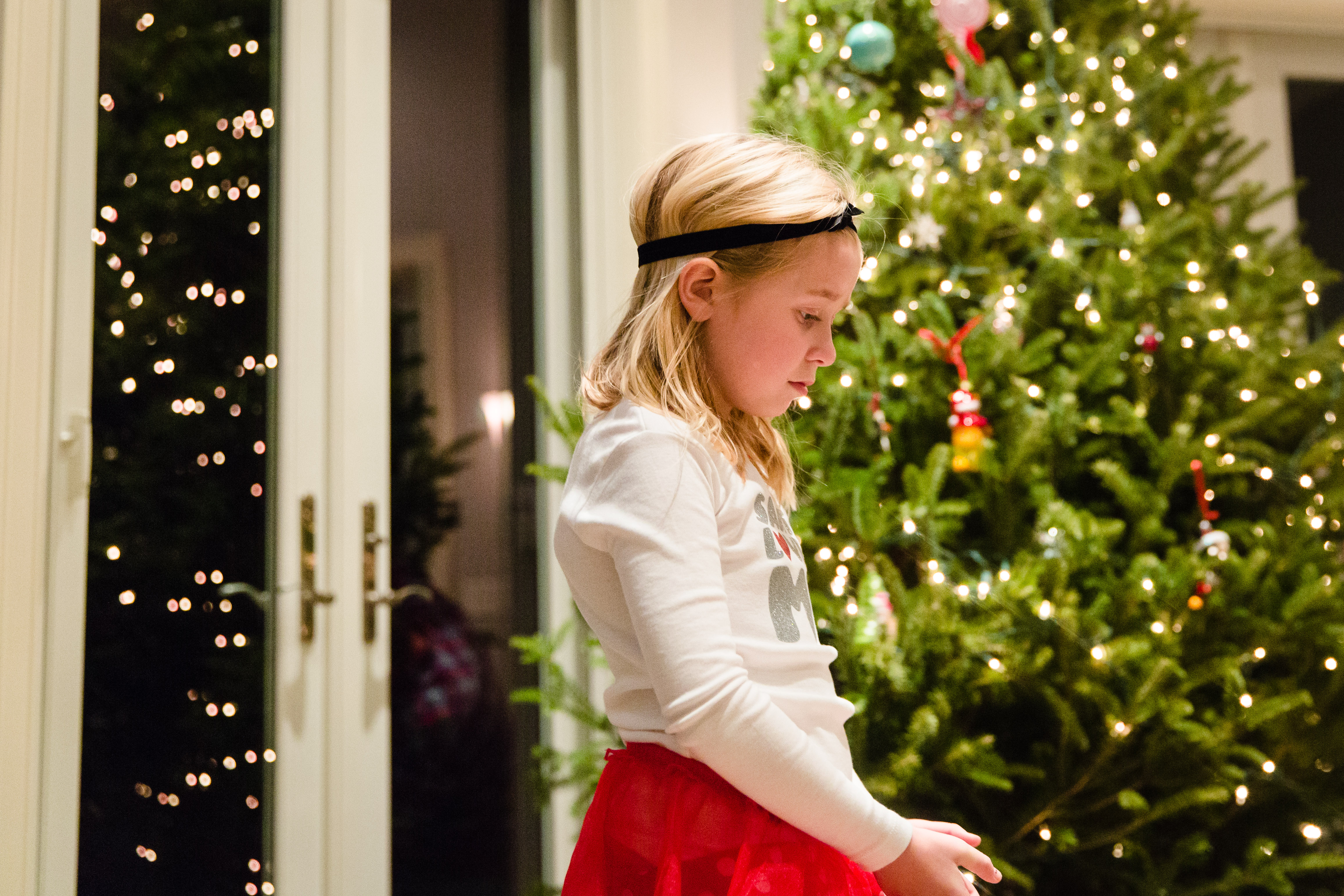 Little girl looking sad with christmas tree in background