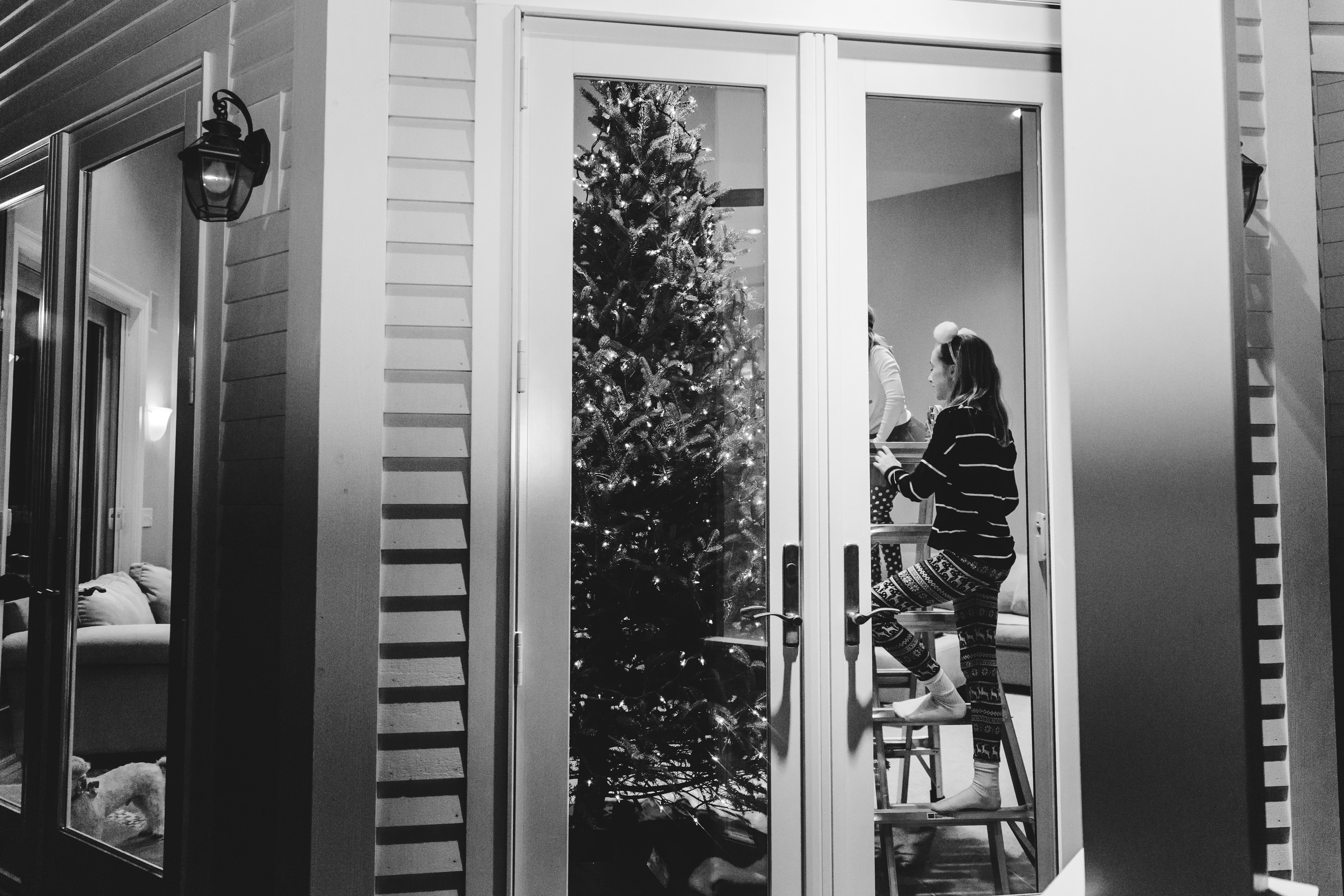 looking in glass doors at girl climbing ladder to decorate Christmas tree