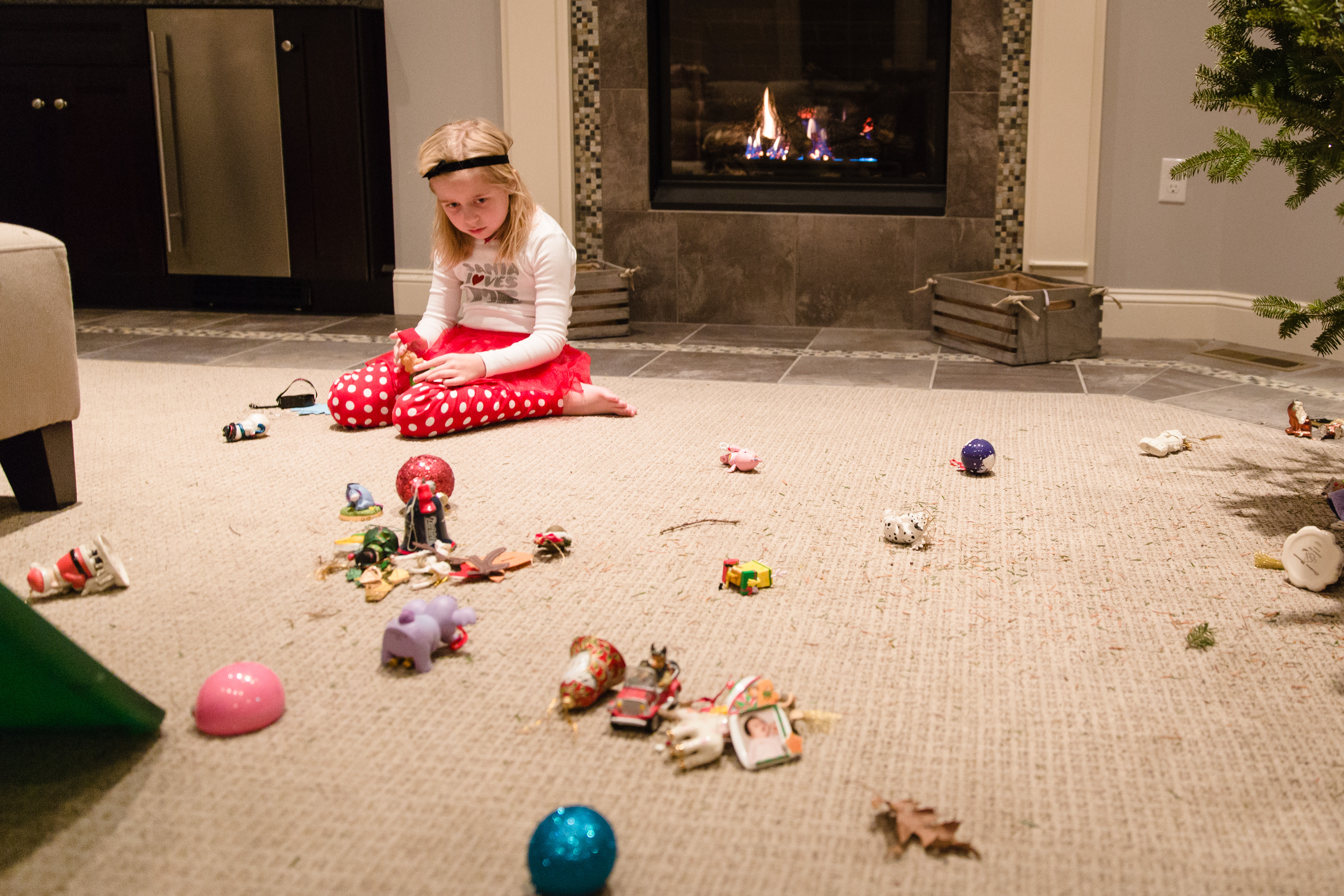 little girl in red and white polka dot tights surrounded by broken ornaments