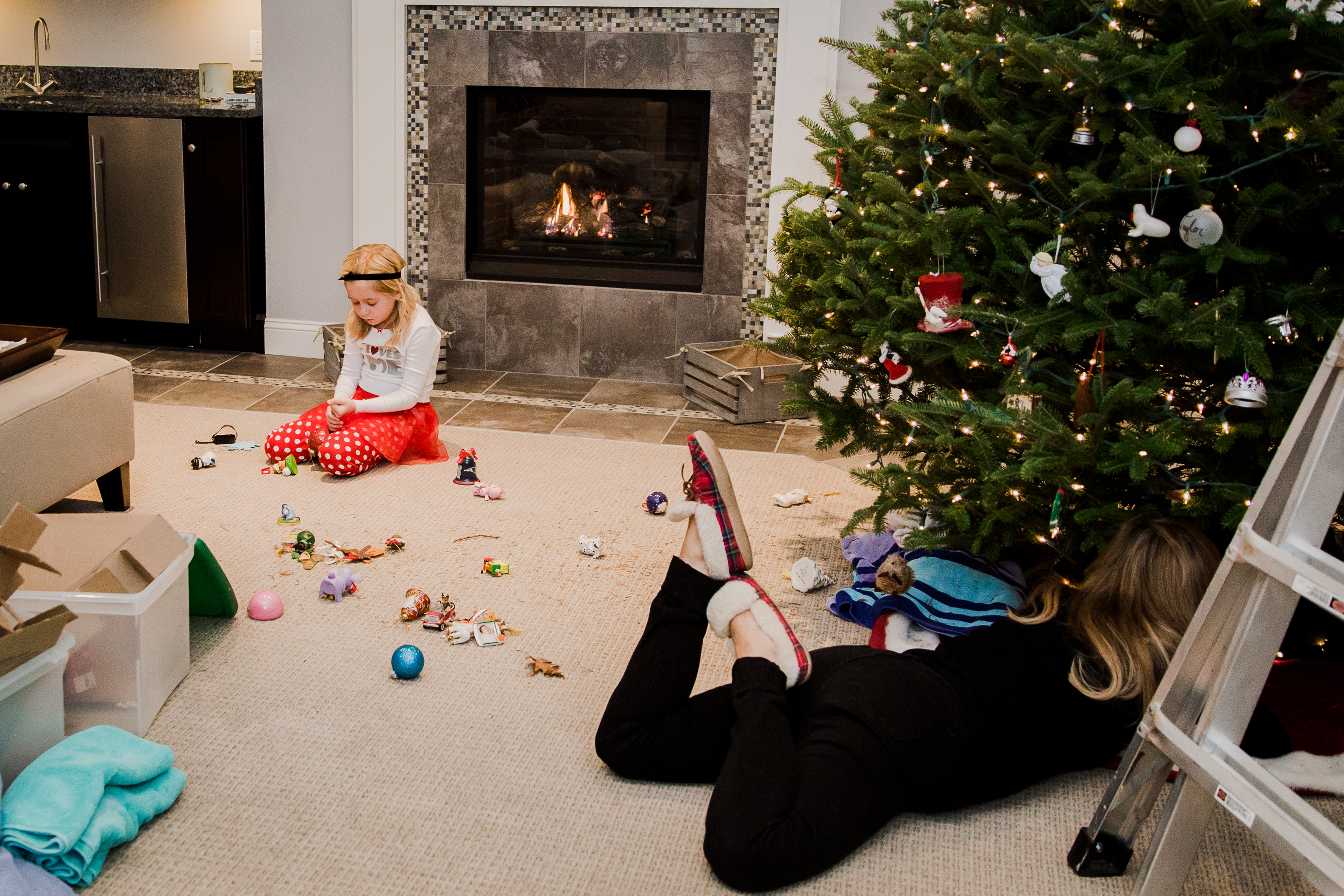 mom laying under tree with little girl and broken ornaments in background
