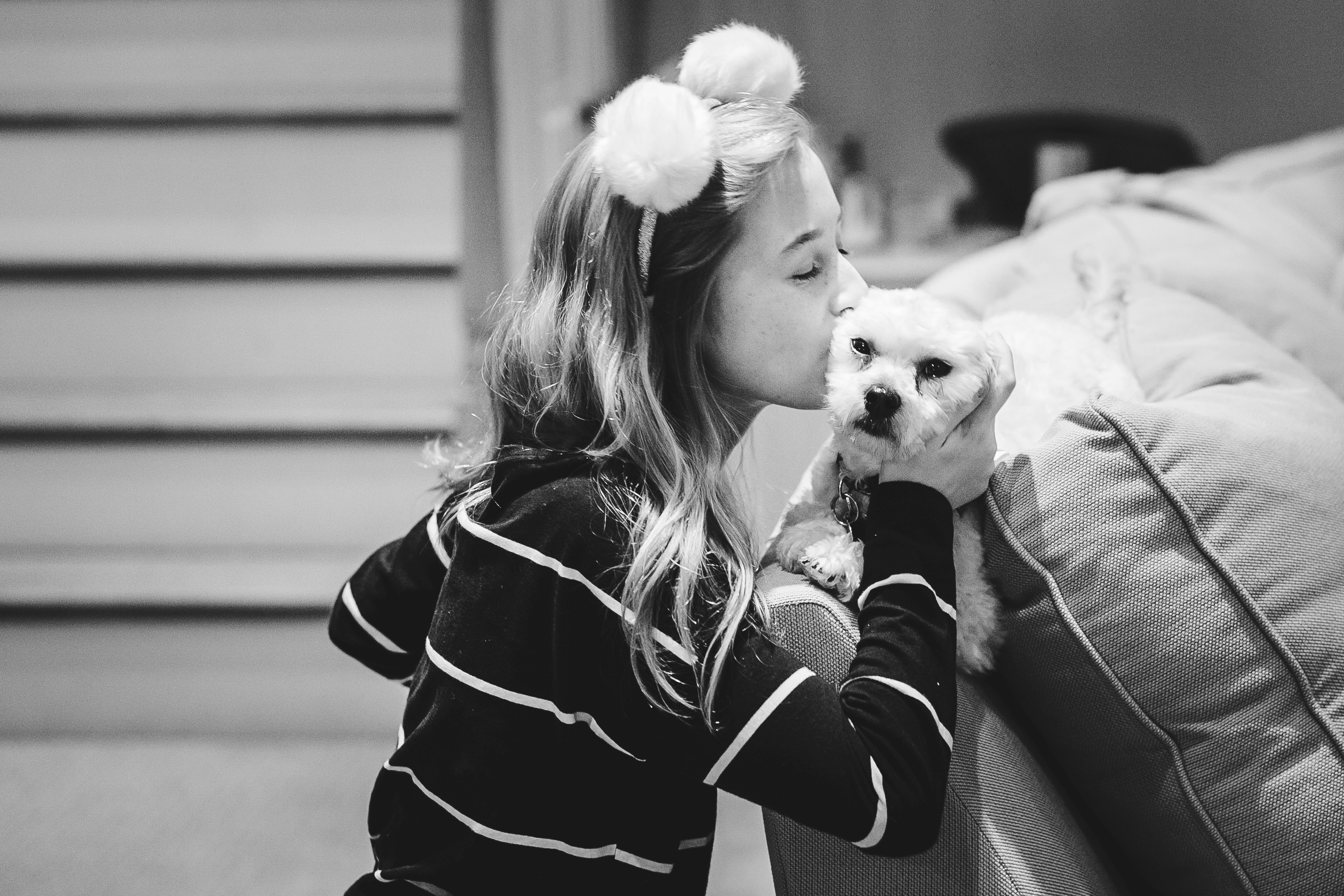 little girl kissing small dog on head