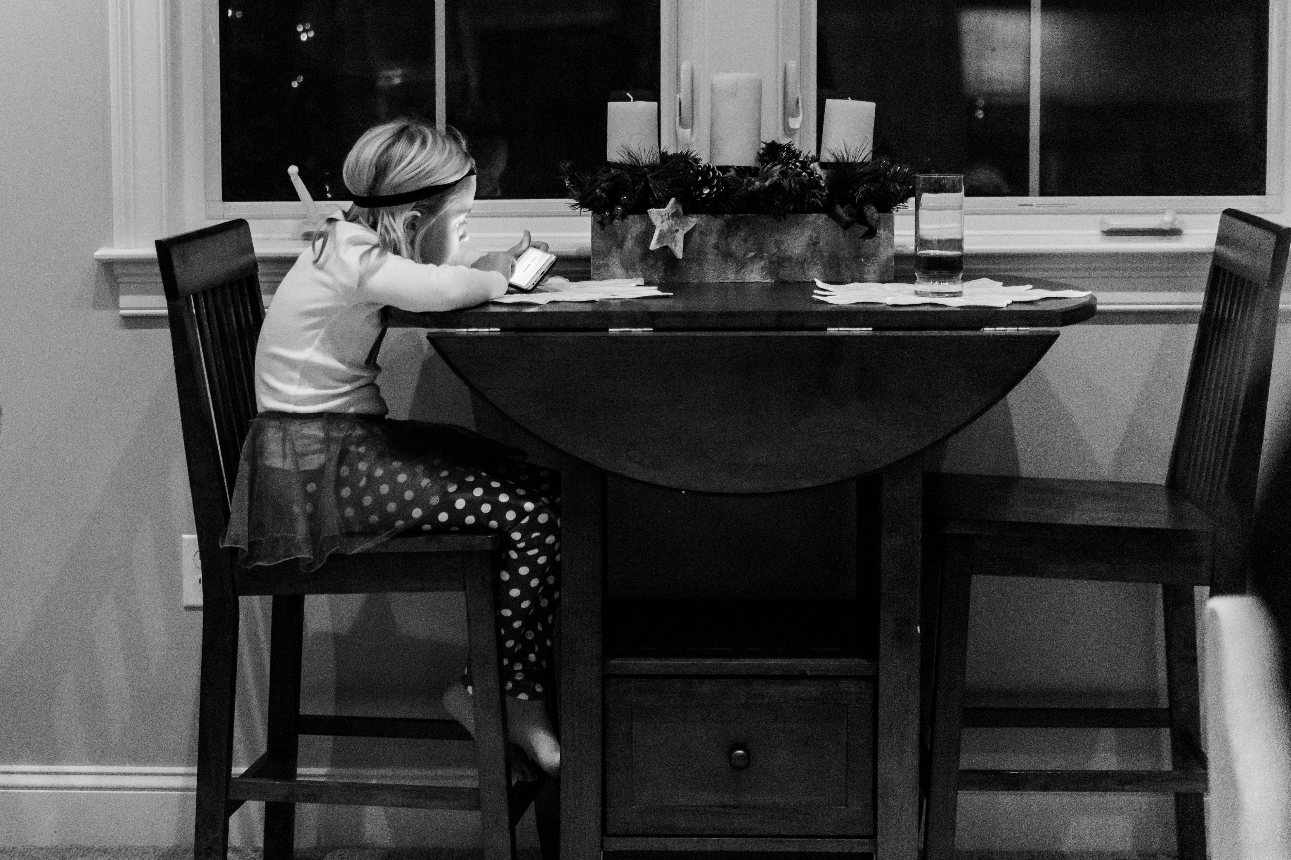 girl at table using iphone