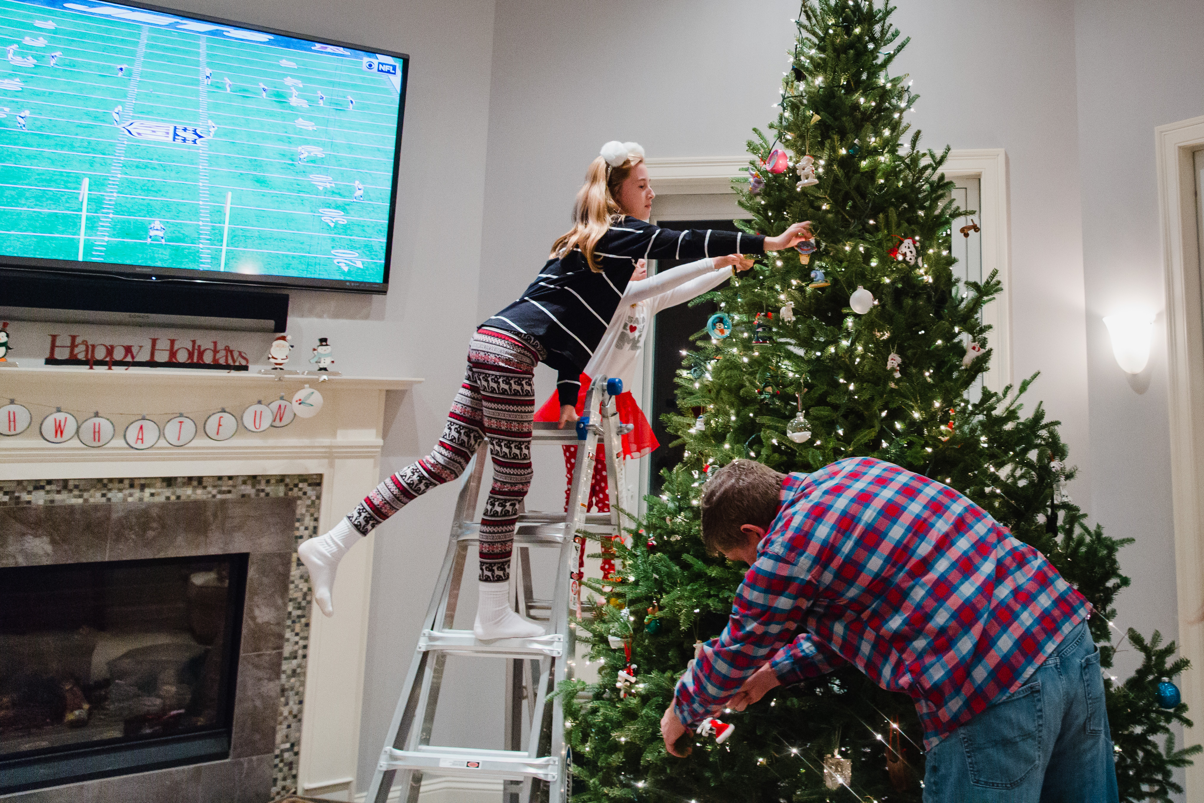 Girl leaning over ladder to hang and ornament on Christmas tree