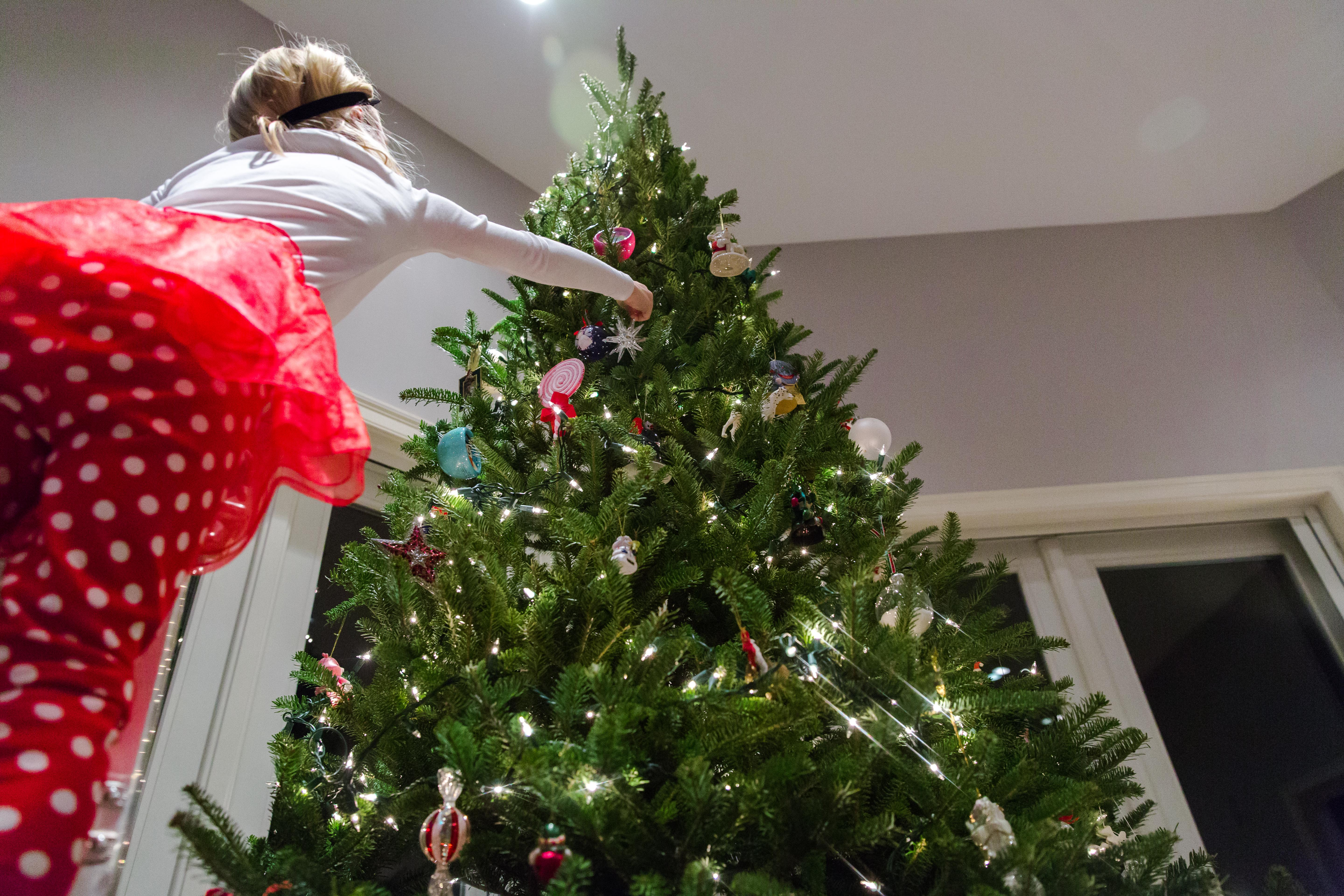 Looking up at little girl hanging silver ornament on Christmas tree