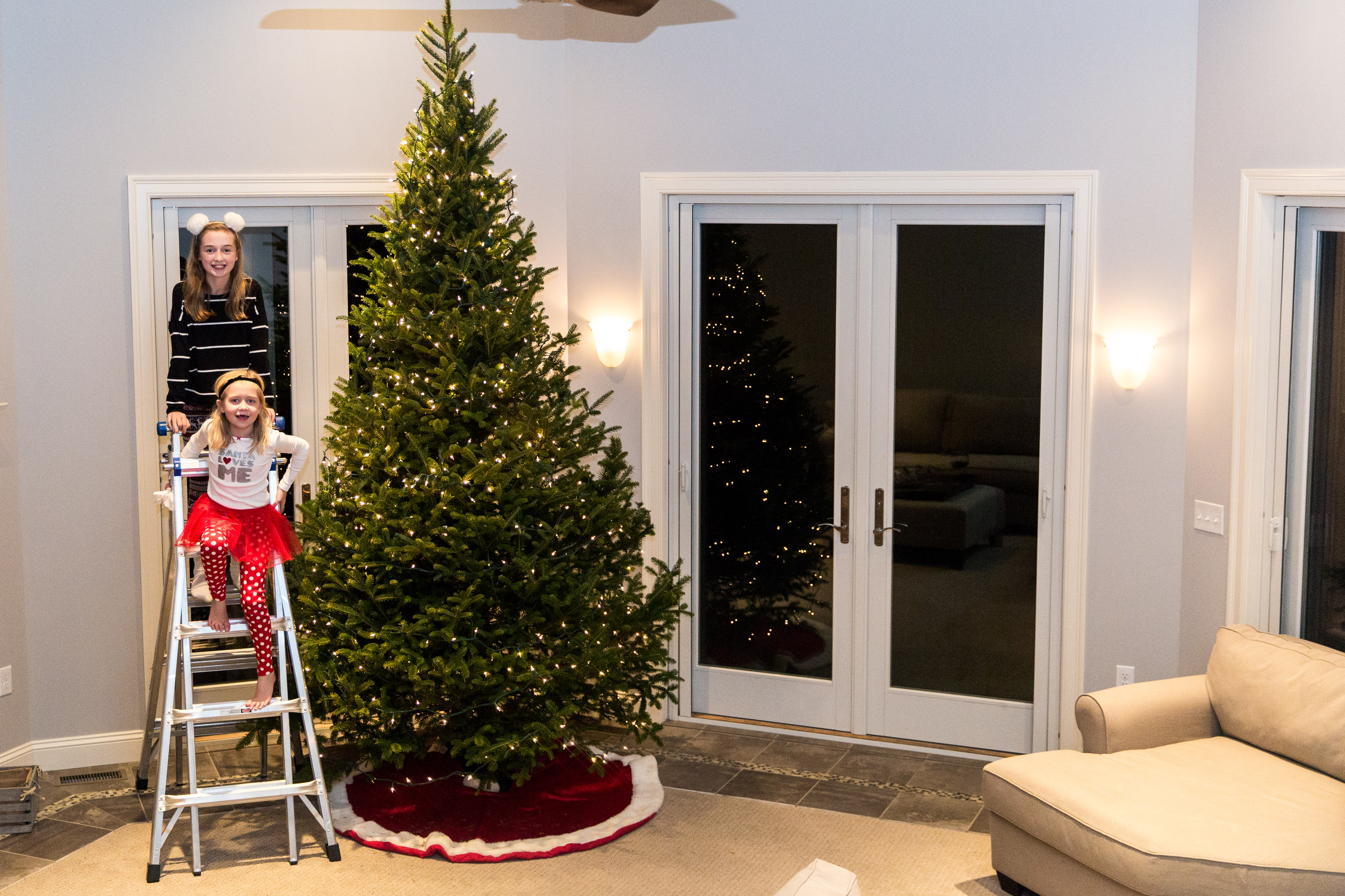 sisters sitting on ladder in front of Christmas tree with lights