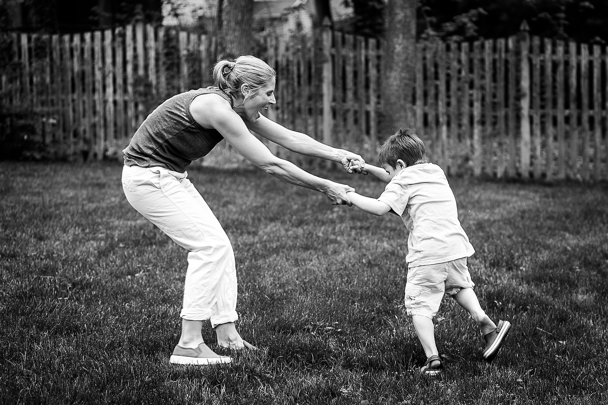 mom laughing and dancing with son in yard