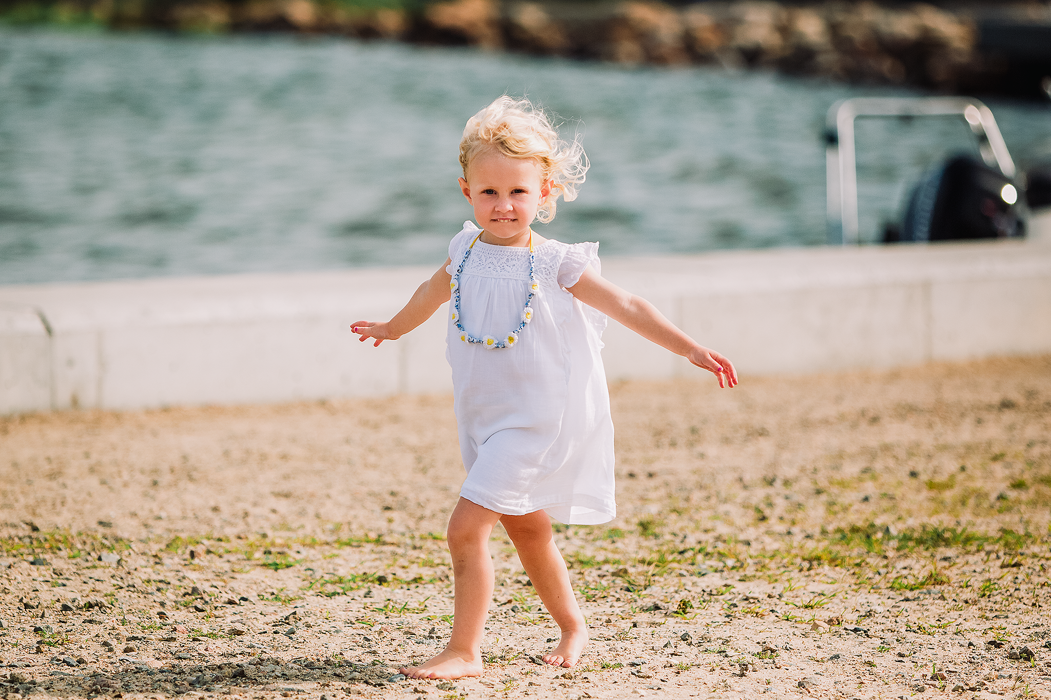 little girl in white dress walking barefoot with arms outstretched