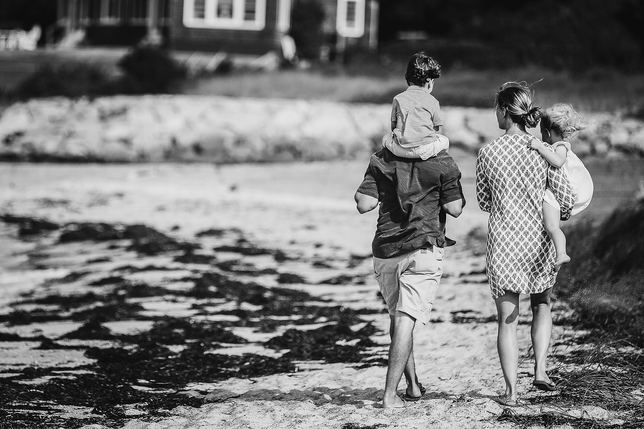 family walking on beach with boy on shoulders and girl in mom's arms