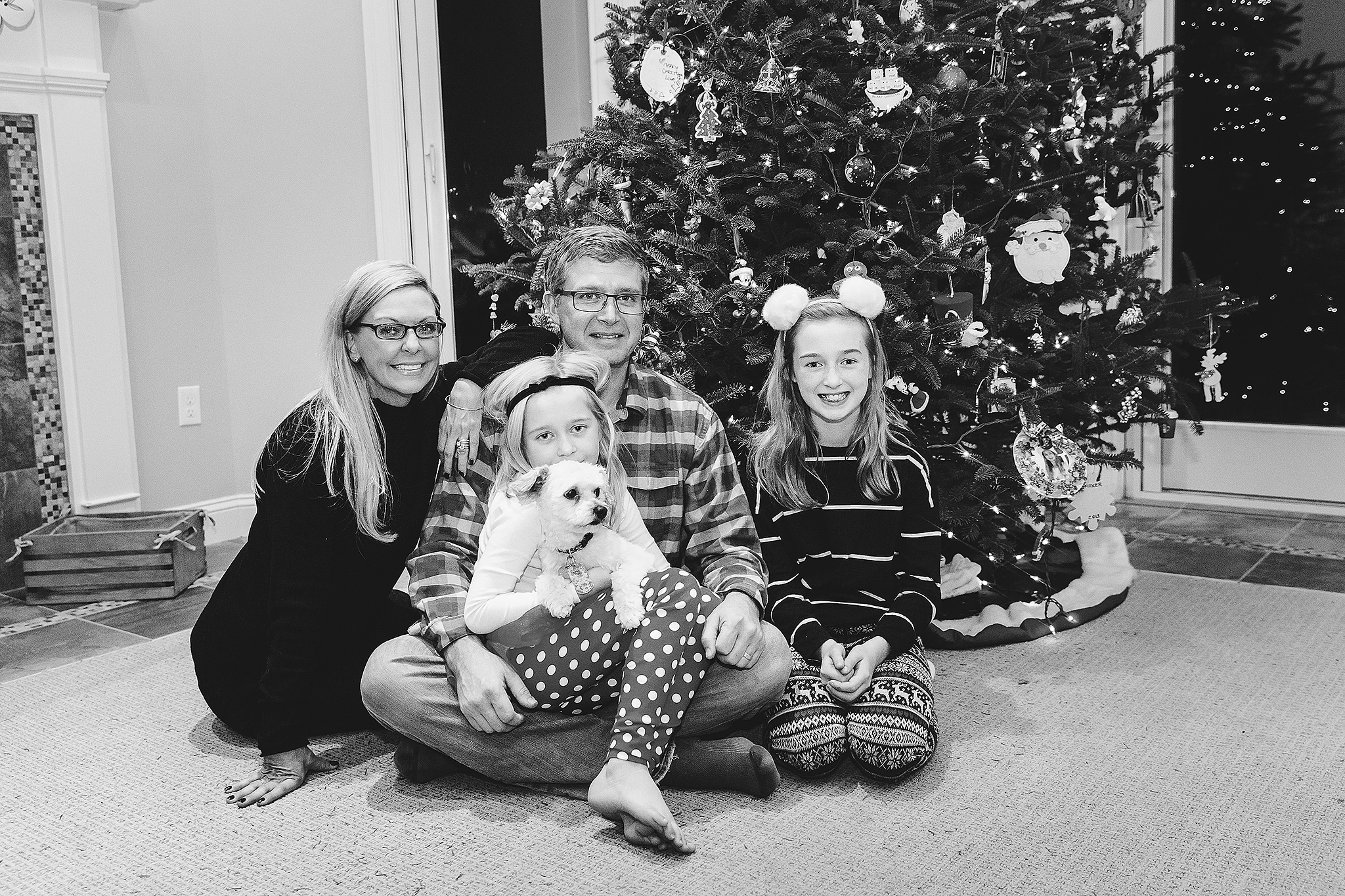 family sitting in front of Christmas Tree with small dog