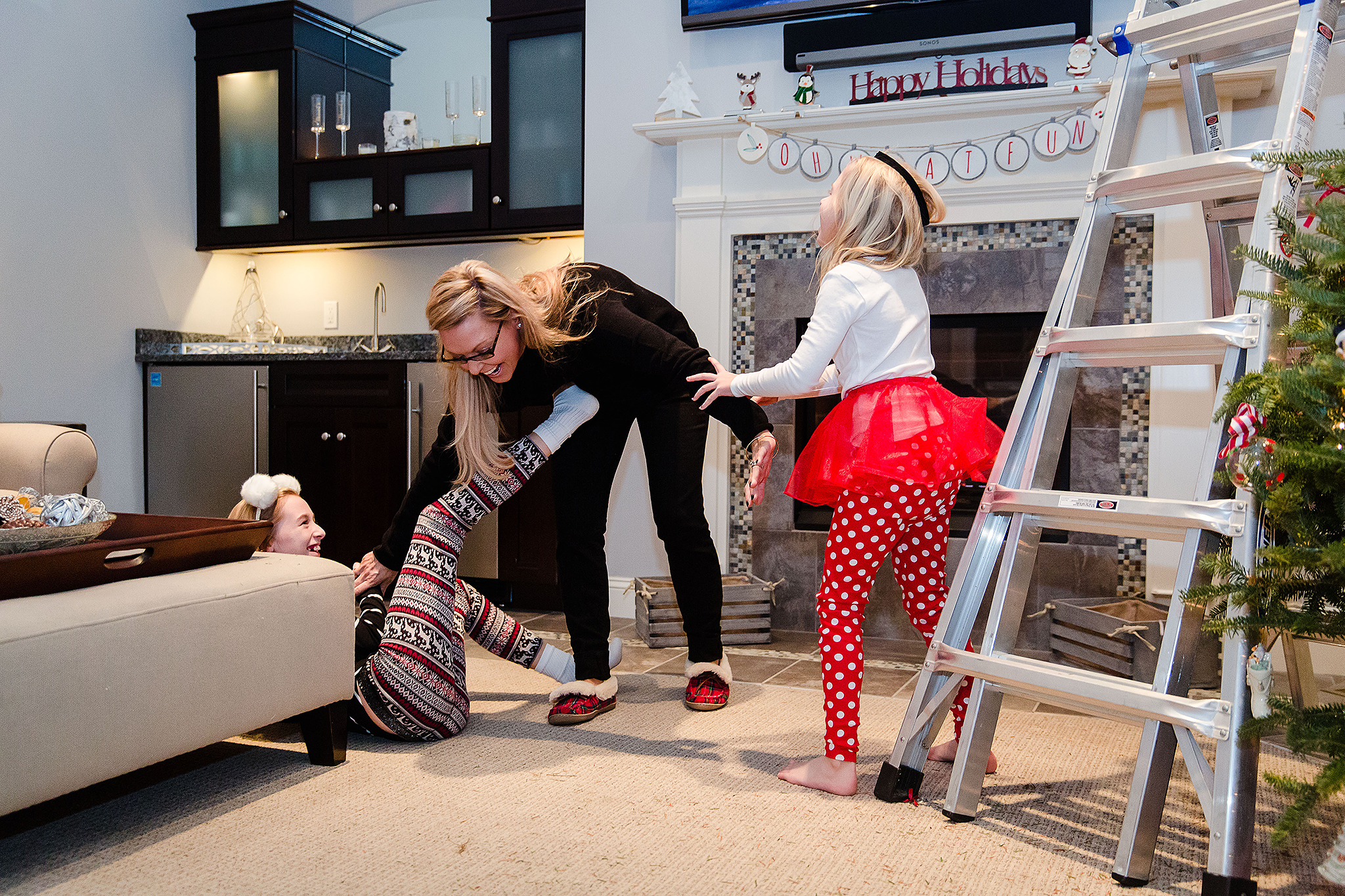 mom playing with daughters and laughing on floor
