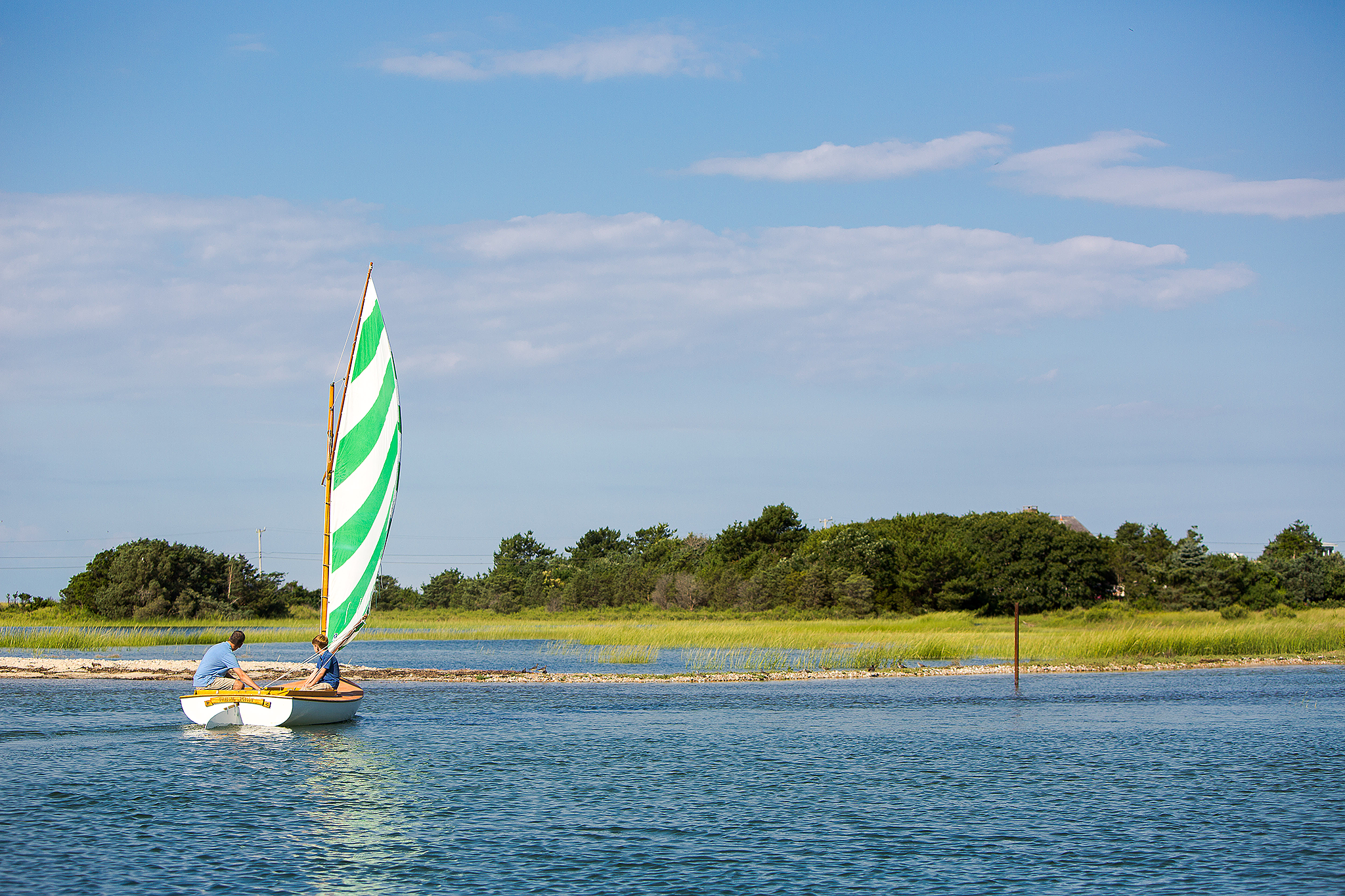 Father and son sailing in shallow water with sea grass