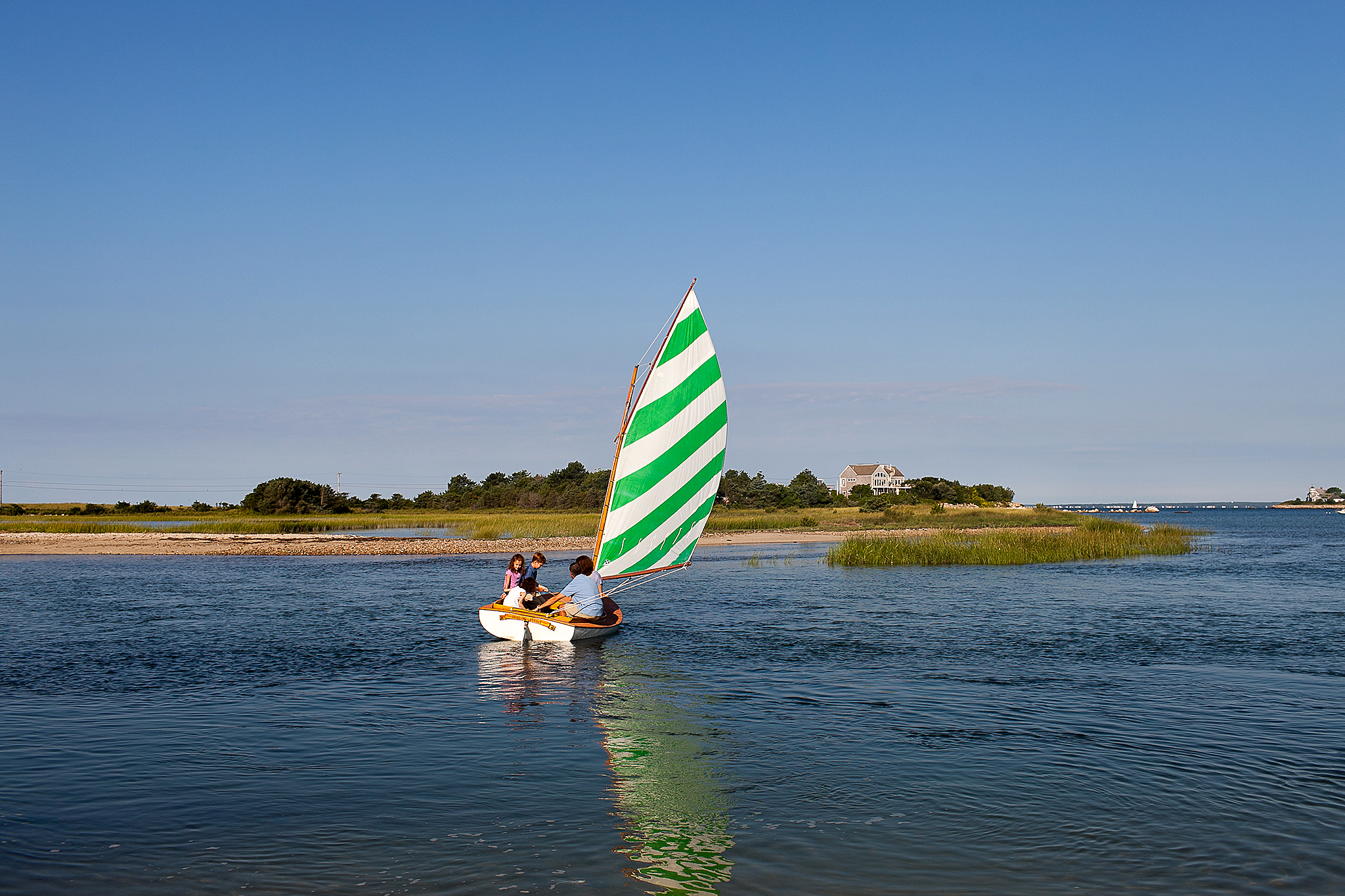 family sailing in Beetlecat with green and white sale