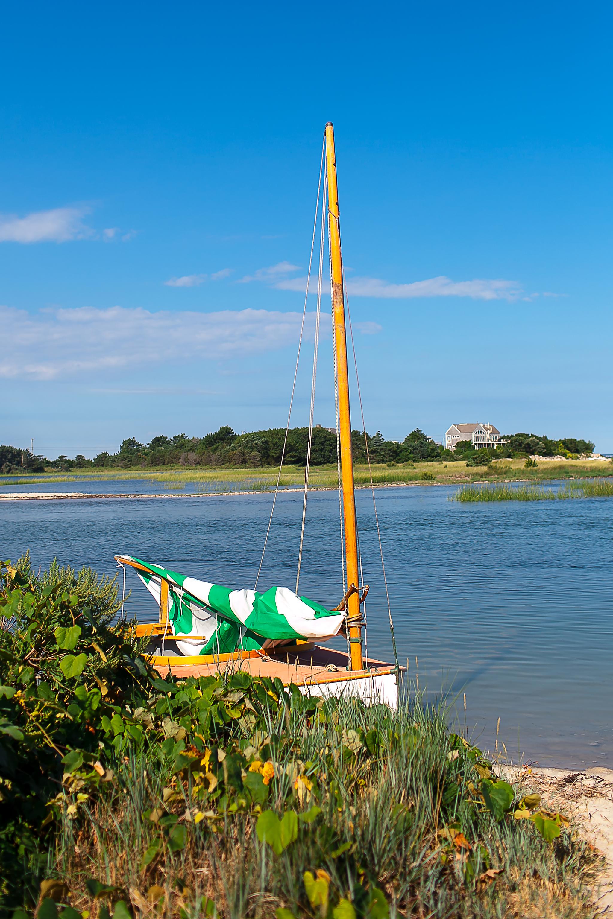 sailboat docked at beach with sail down