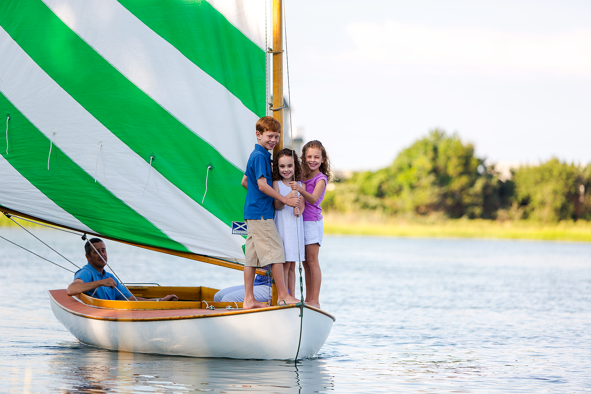 brother and sisters standing in front of sailboat while dad watches