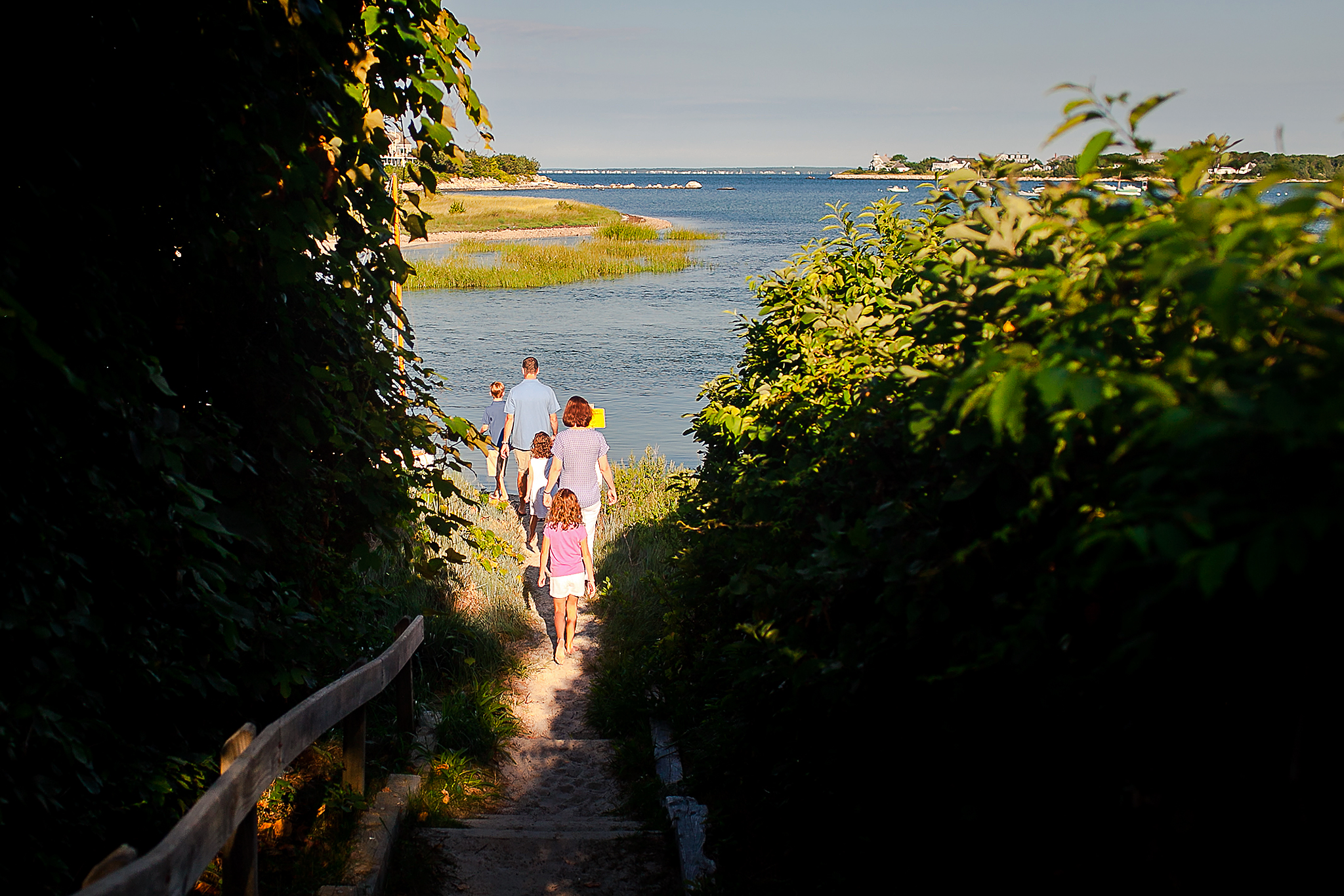 family walking down path to beach