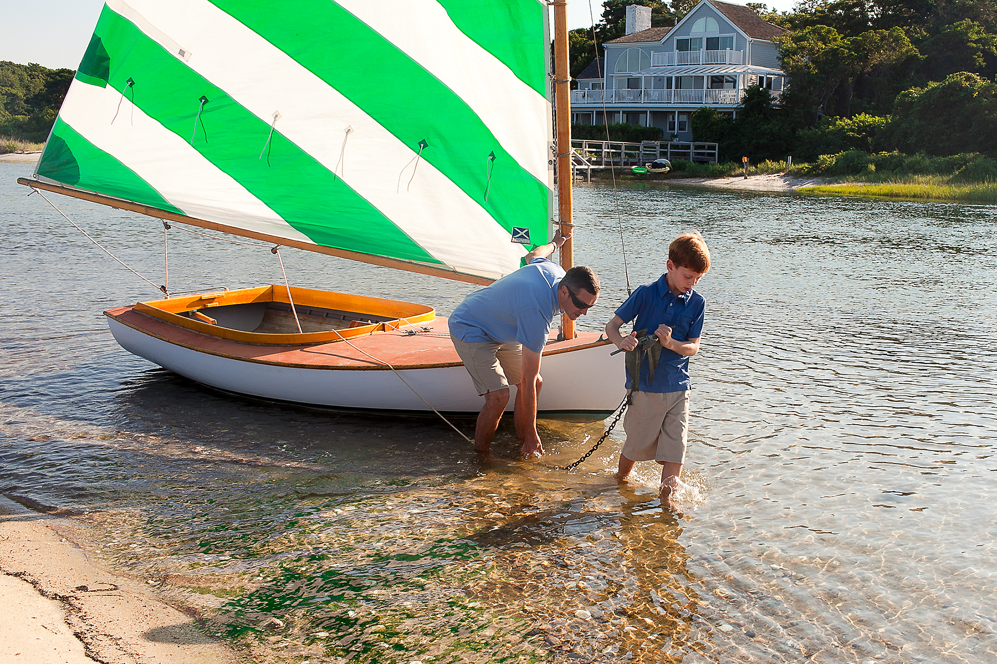 dad and son putting anchor in water