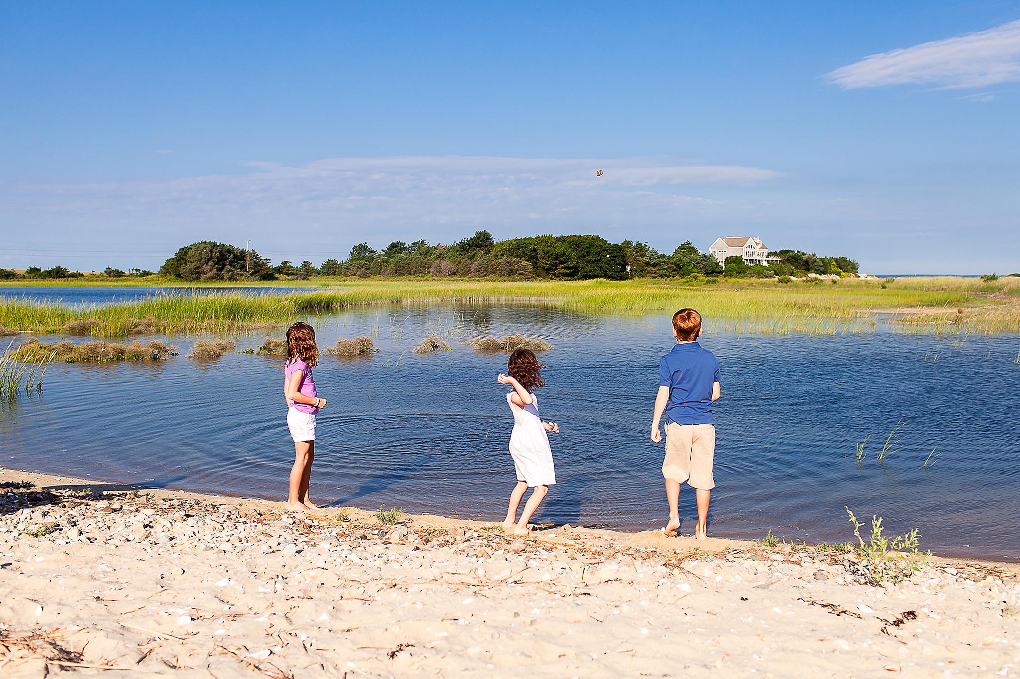 siblings standing on shore throwing rocks in water