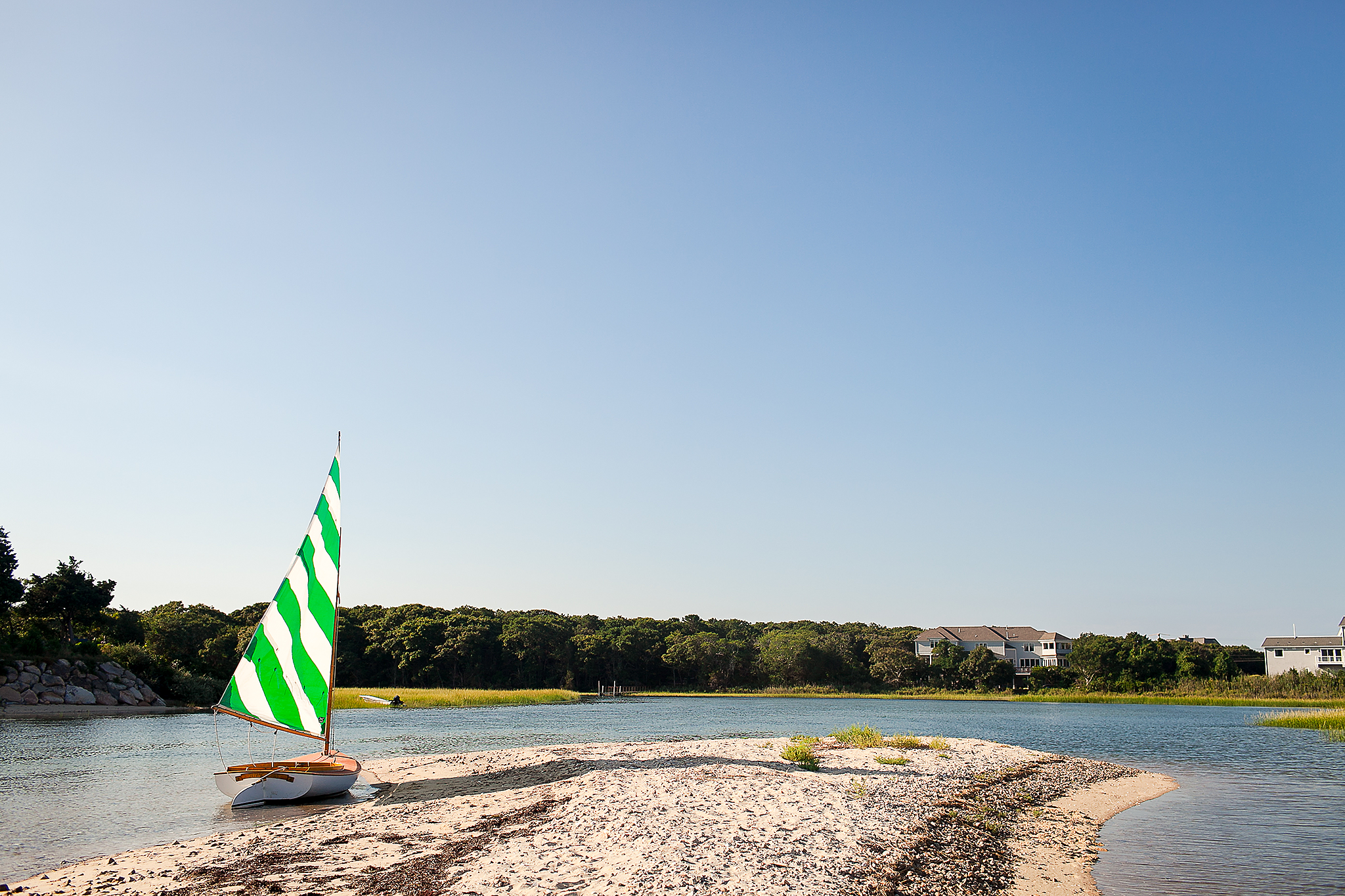 Sailboat on shore with green and white sale