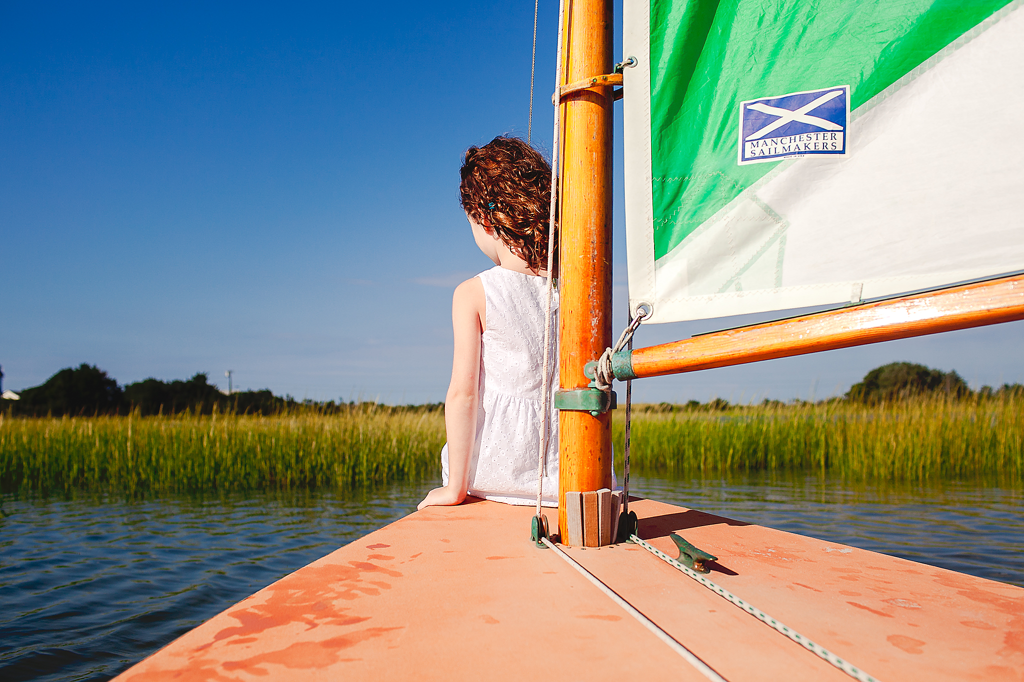 little girl in white dress sitting on front of sailboat heading towards sea grass
