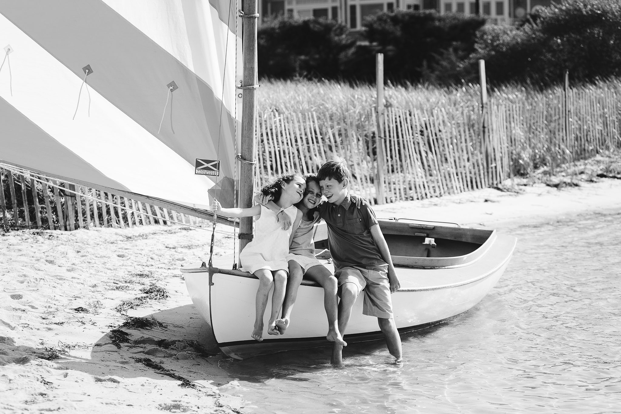 brother and sisters laughing on front of sailboat