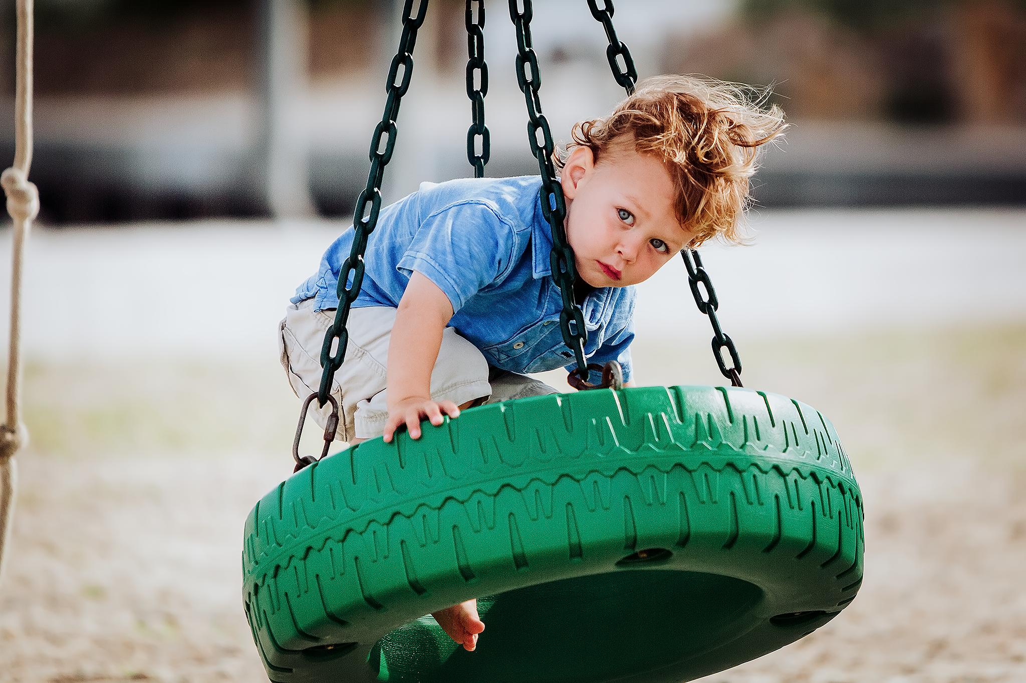 Little boy on green tire swing