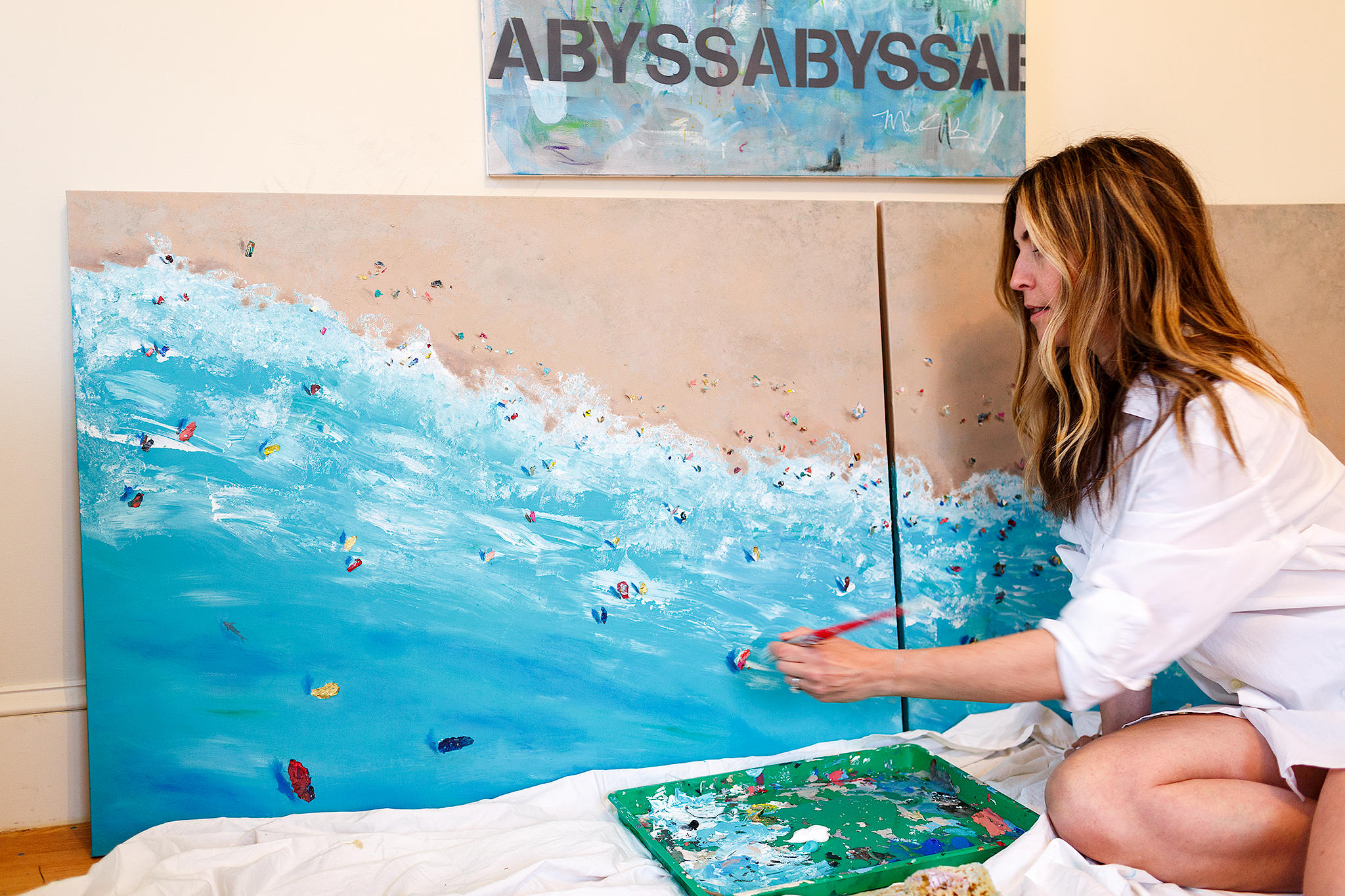woman painting ocean on canvas
