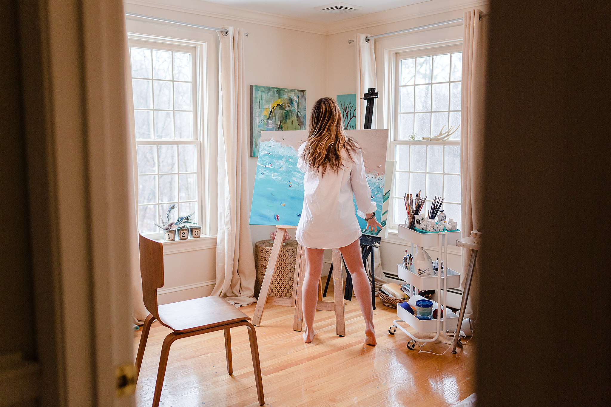 woman standing in room painting canvas