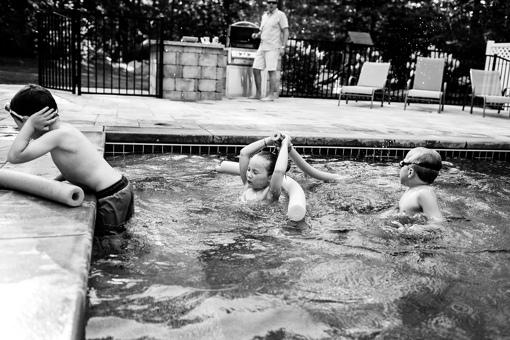 siblings fighting with water noodle in pool Seacoast NH family photographer