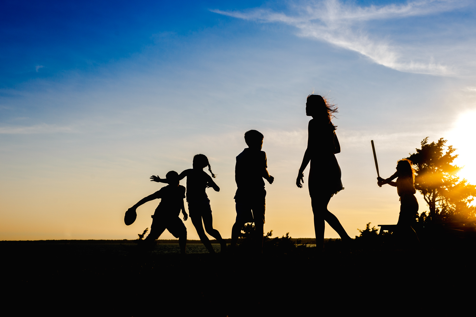 silhouette of kids playing sports