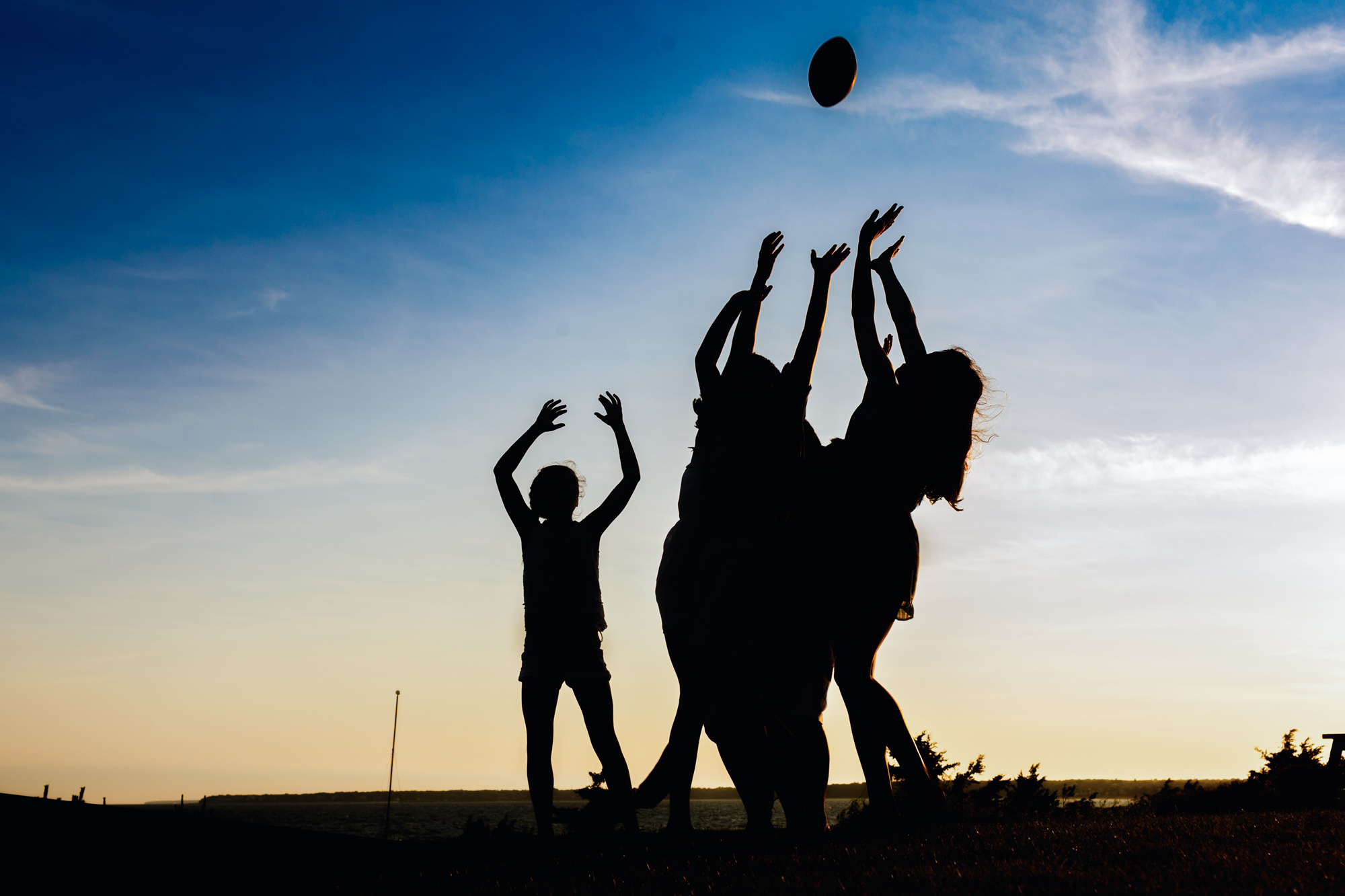 silhouette of kids jumping for football