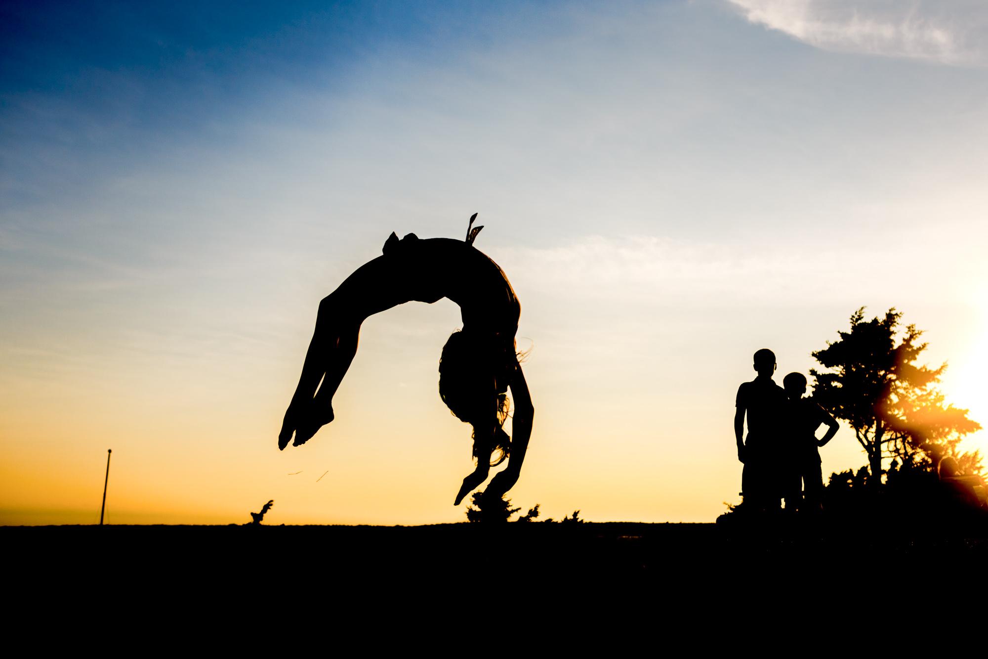 silhouette of girl doing back flip