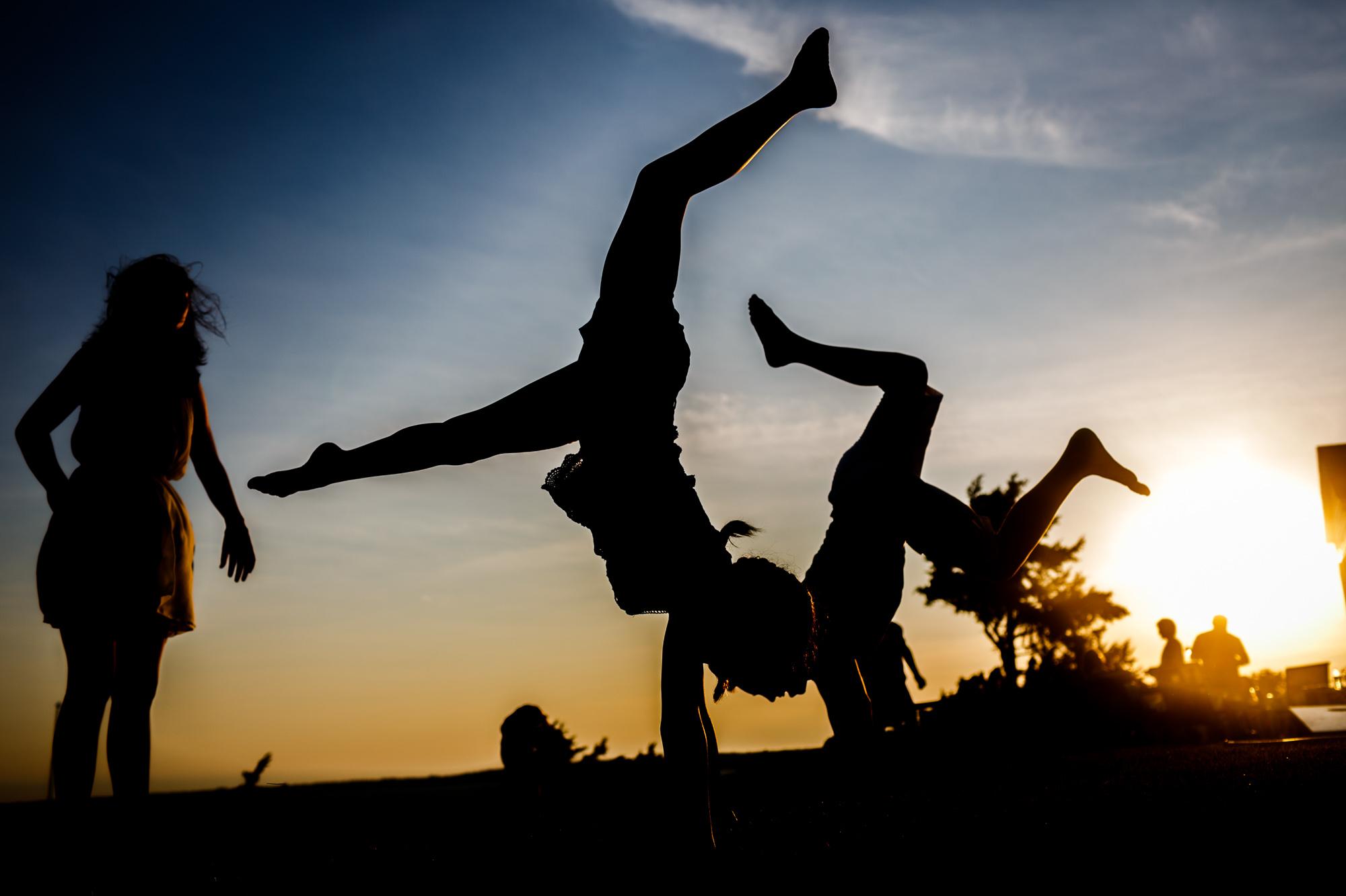 silhouette of kids doing handstands