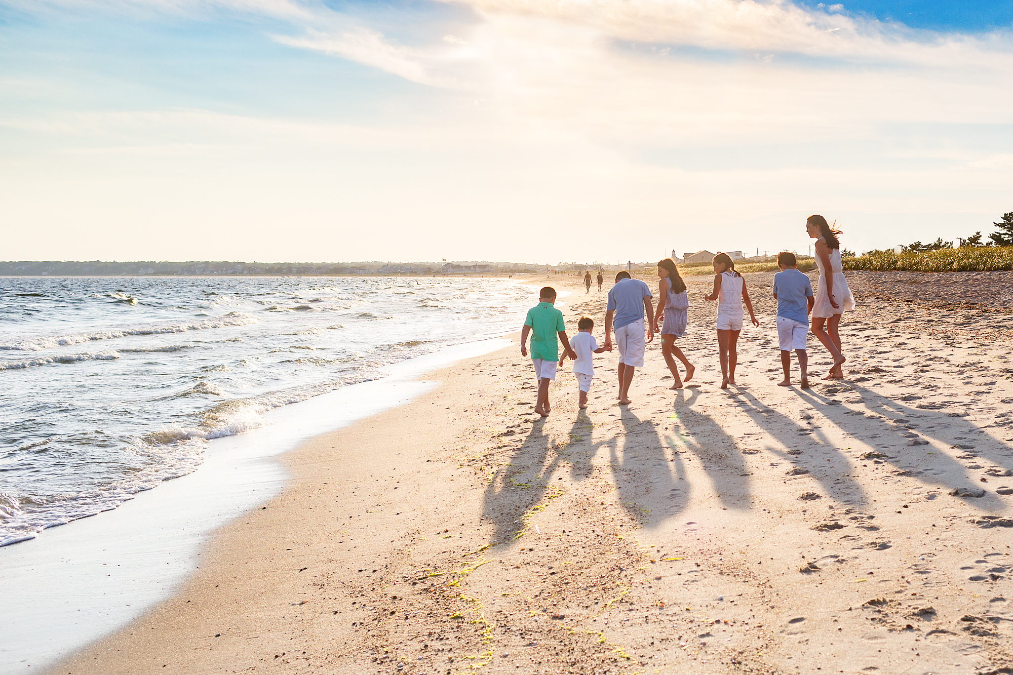 back of cousins walking on beach
