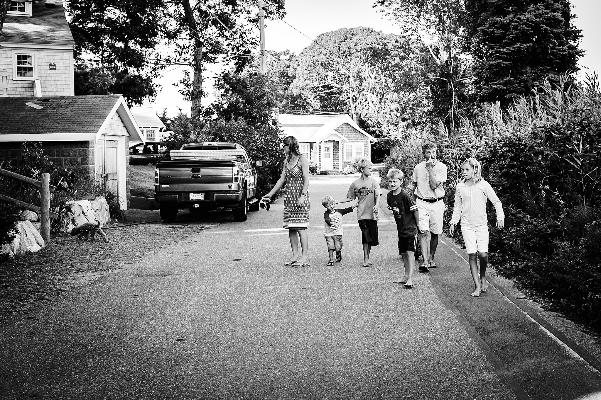 family walking down street black and white