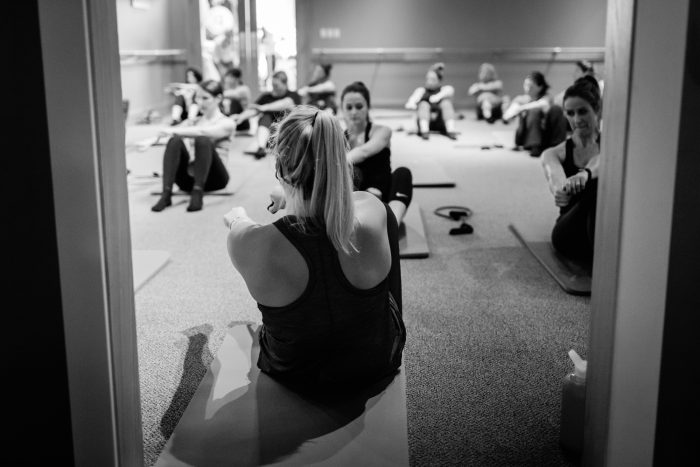 women at barre class doing situps