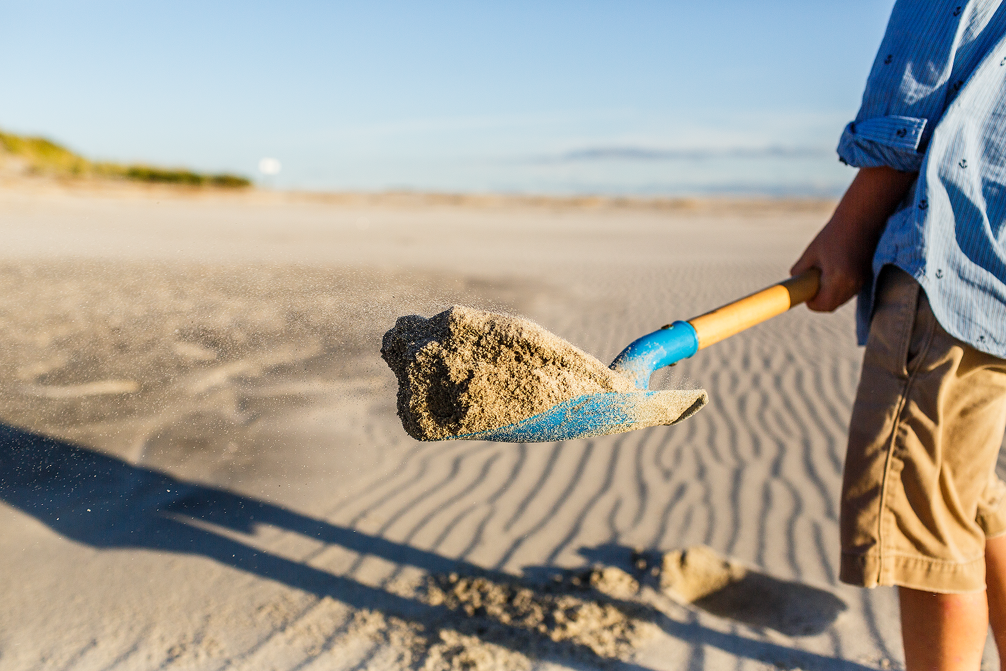 shovel of sand blowing at beach