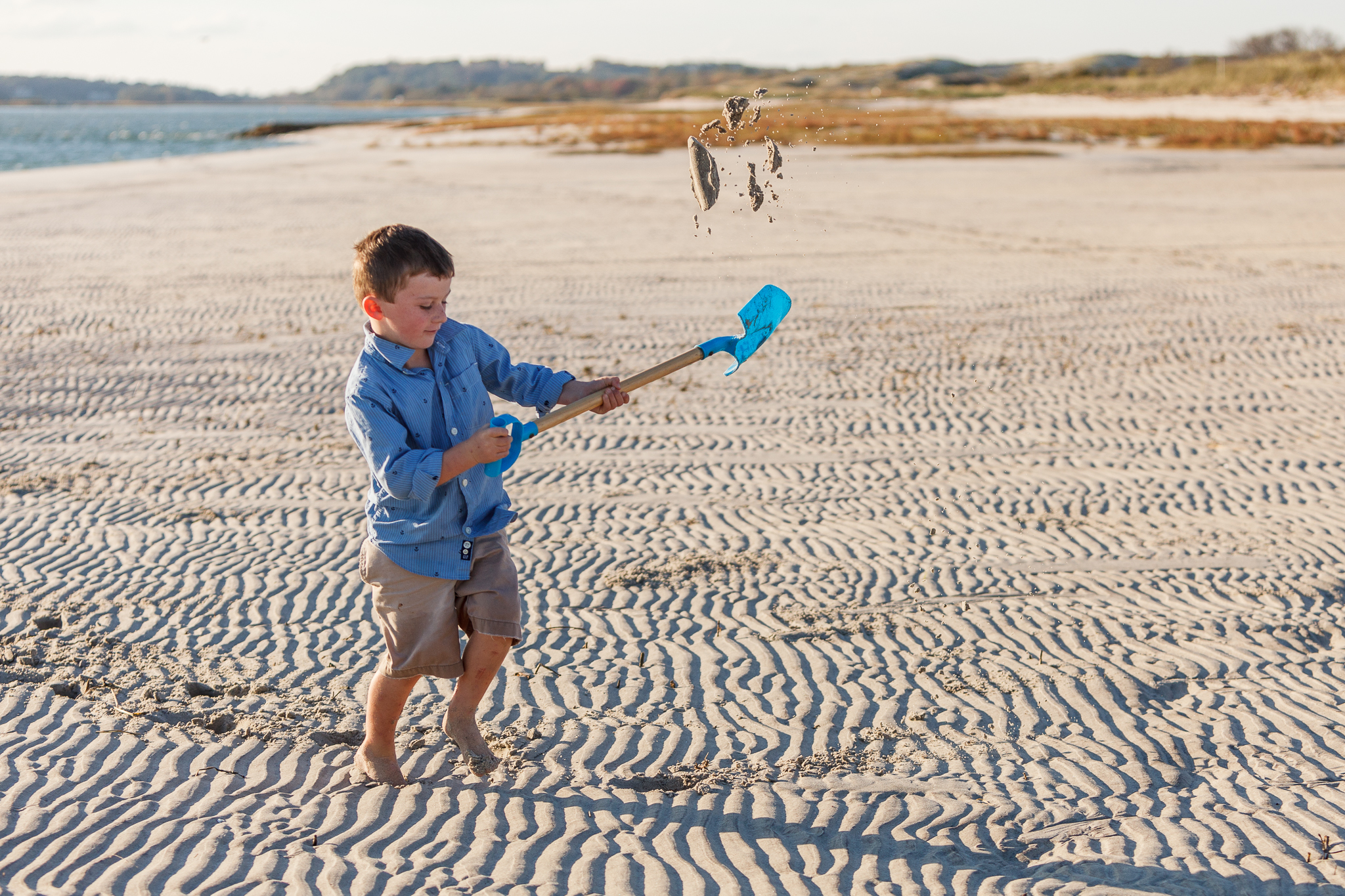 boy on beach flinging sand with a shovel