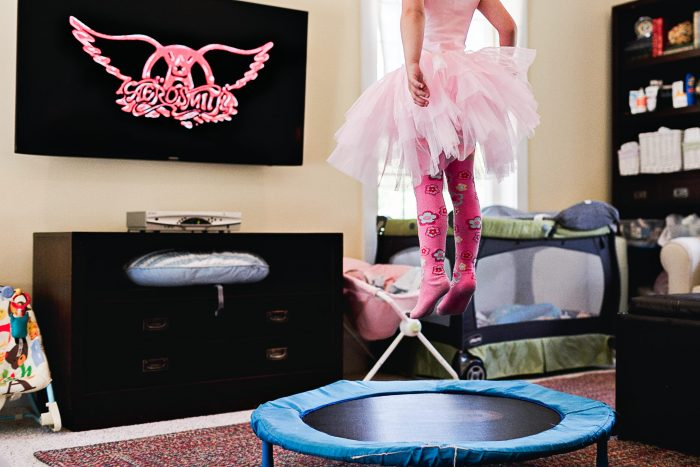 lower half of little girl's body in pink tutu jumping on trampoline