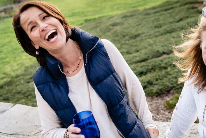 Brunette woman wearing white shirt blue vest and gold jewelry laughing outside holding a blue glass