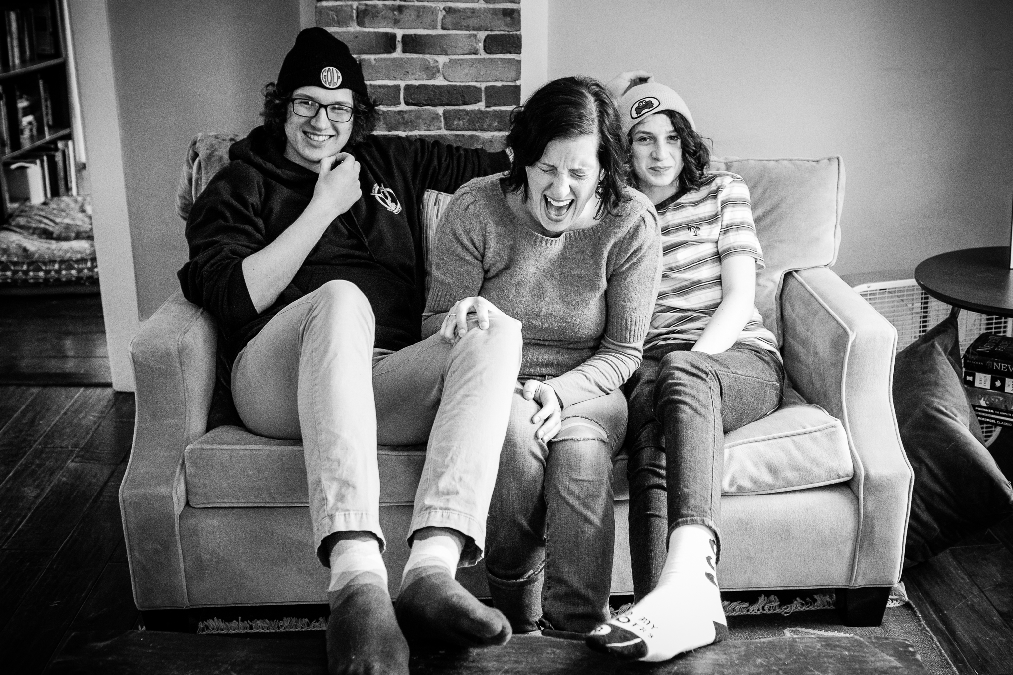 mom sitting between two teenage sons laughing