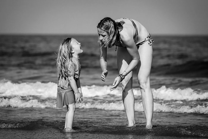 little girl crying at beach while mom tries to comfort her