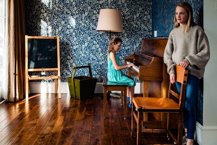 young girl playing piano while sister stands at wall