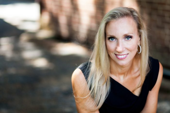 beautiful woman smiling by brick wall for headshot