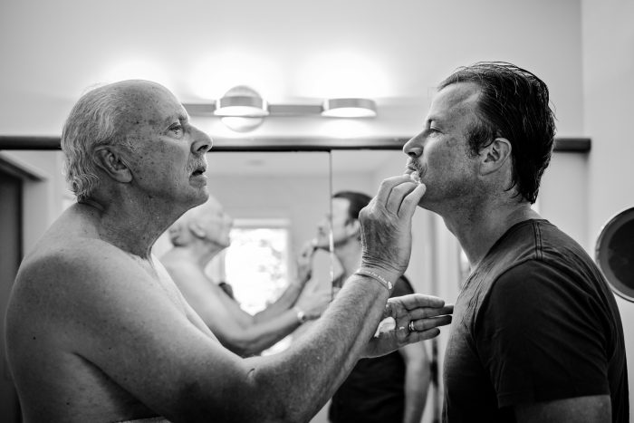 older father helping adult son shave in bathroom
