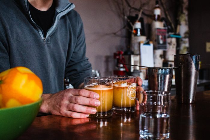 bar scene with two hands holding a glasses of whiskey sours